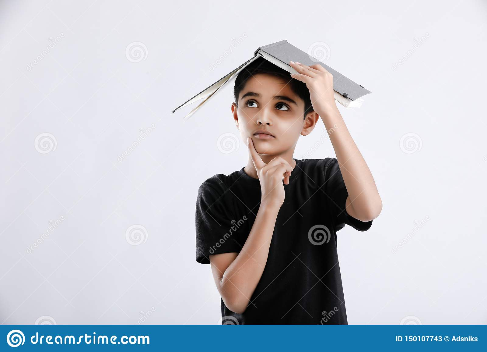 маленький индийский/азиатский мальчик с книгой на голове и мысли серьезной