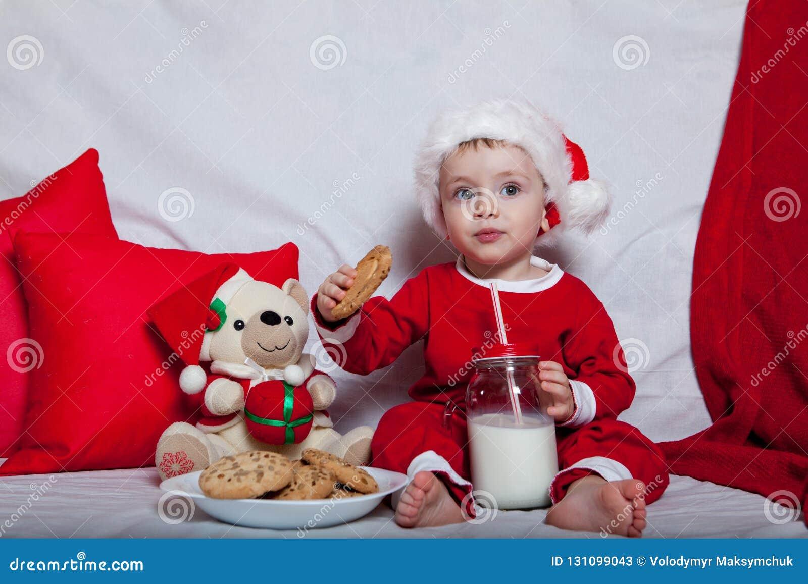 Маленький ребенок в красной крышке ест печенья и молоко Фотография рождества младенца в красной крышке Праздники и рождество Ново