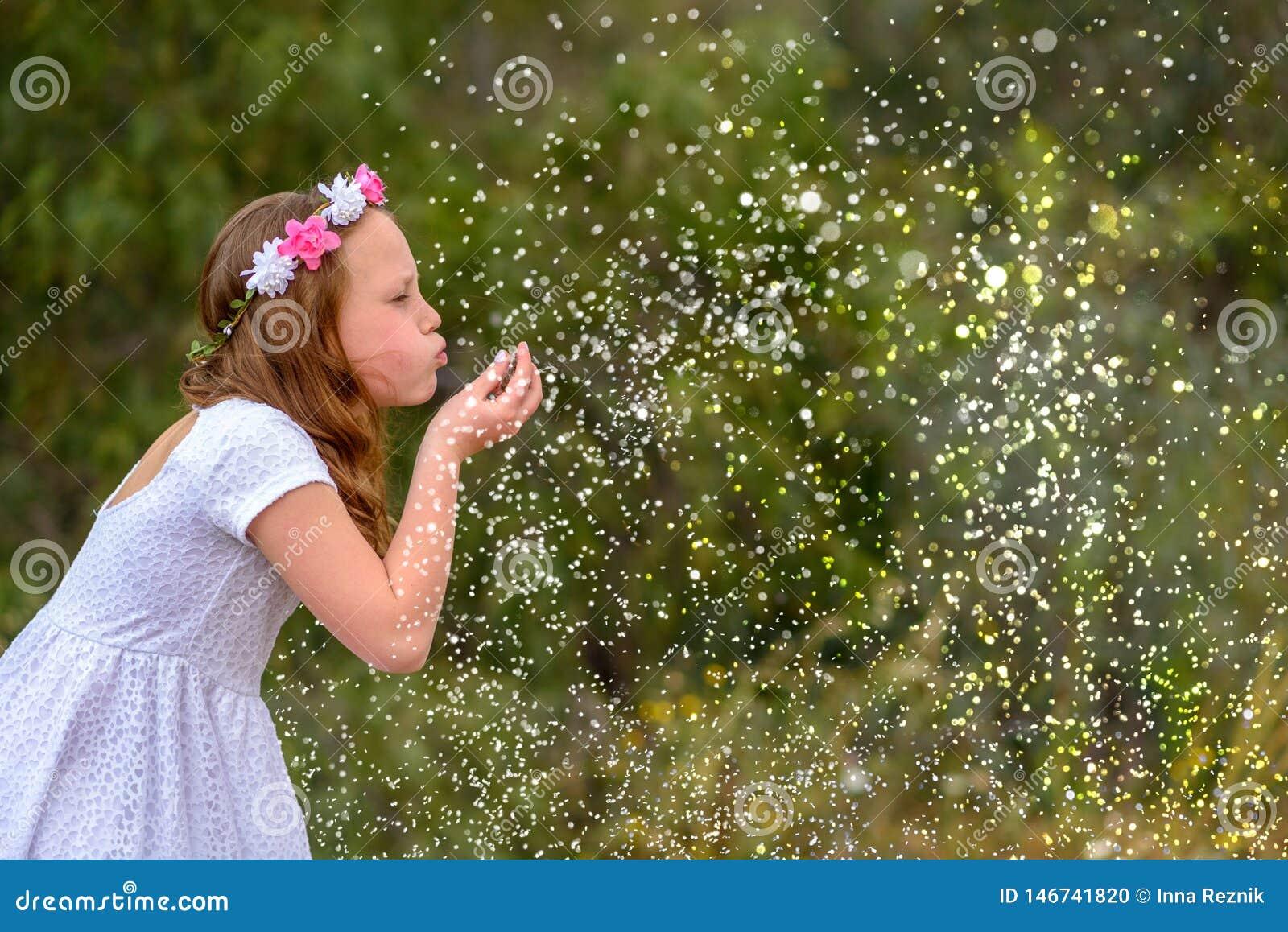 Маленький ребенок дует сверкнает или снежинки в предпосылке природы, концепция праздника