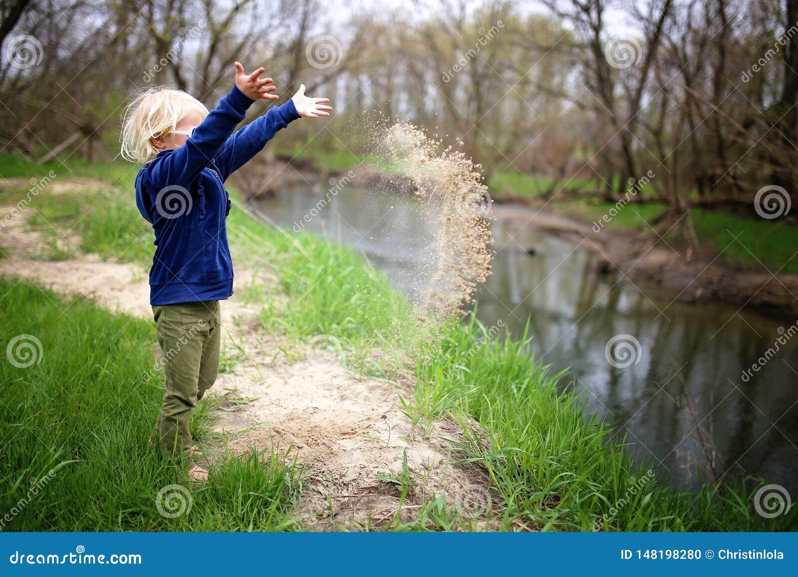Маленький ребенок играя снаружи рекой, бросая песком в воде