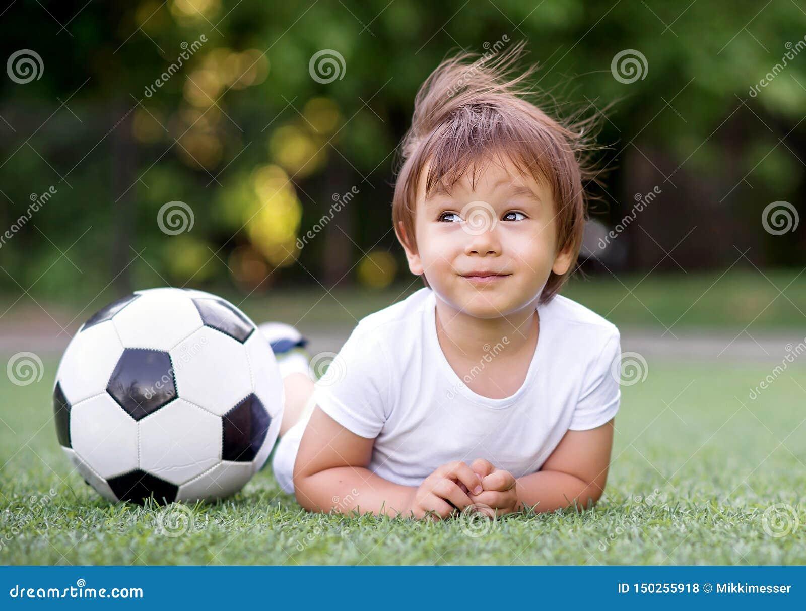 Маленький ребенок малыша кладя на живот на футбольном поле около футбольного мяча и мечтать Ветер развевает волосы ребенк Будущий