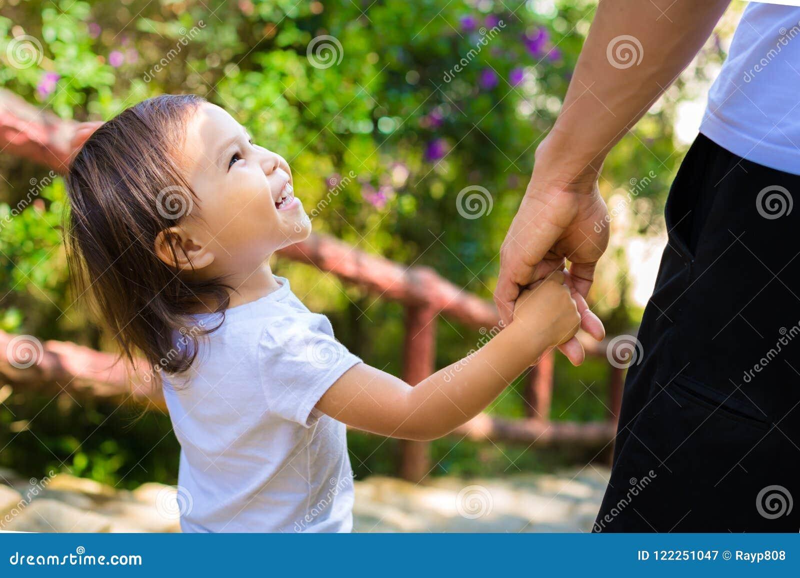 Маленький ребенок смотрит вверх счастливо на ее отце пока они идут через парк держа руки