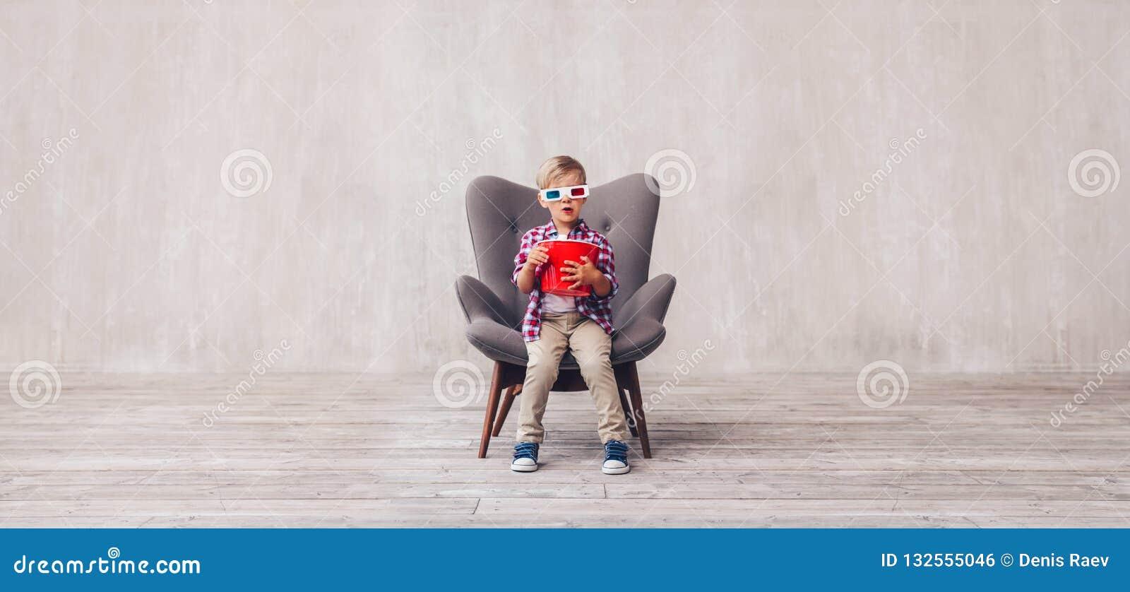 Маленький ребенок с попкорном в стеклах 3d