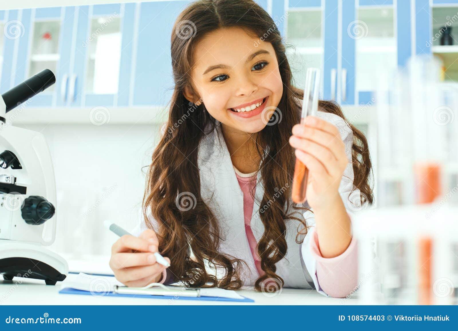 Маленький ребенок с учить класс в лаборатории школы держа усмехаться пробирки