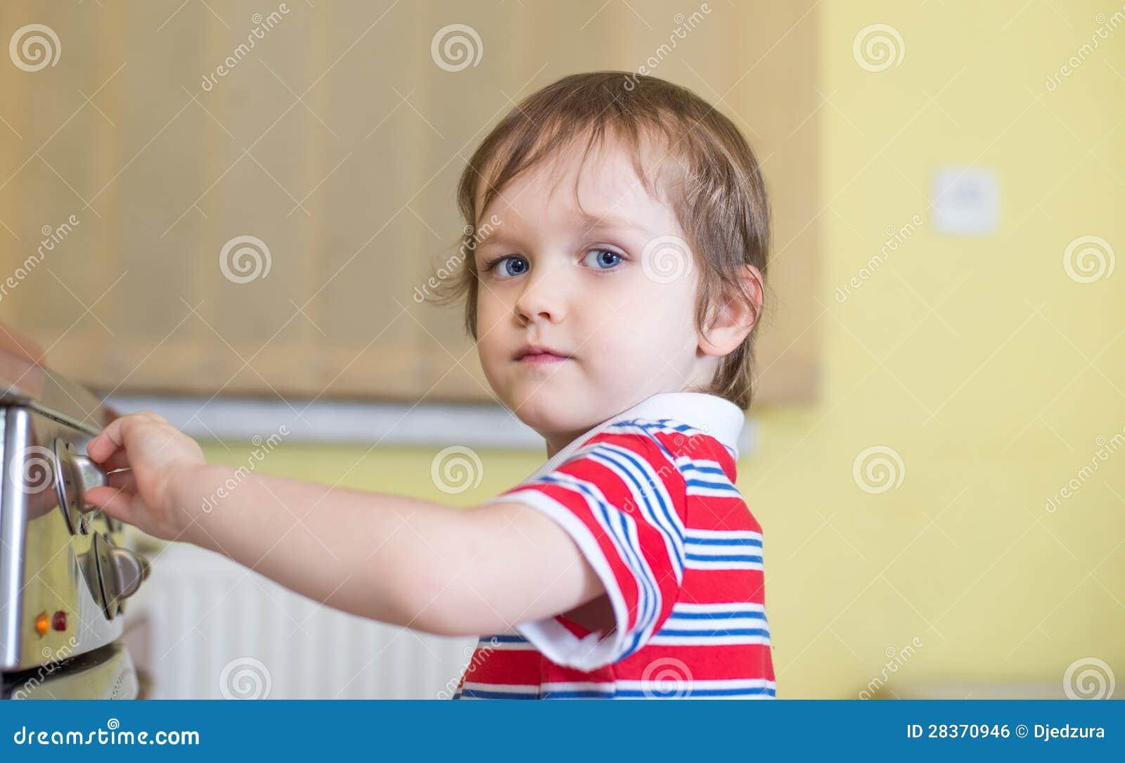 Маленький ребёнок касающий плита - опасность в доме