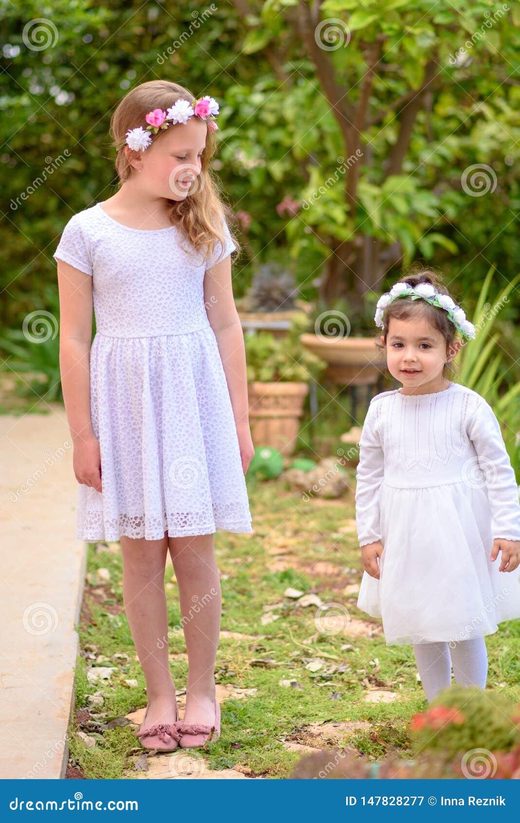 2 маленькой девочки в белых платьях и венке цветка имея потеху сад лета