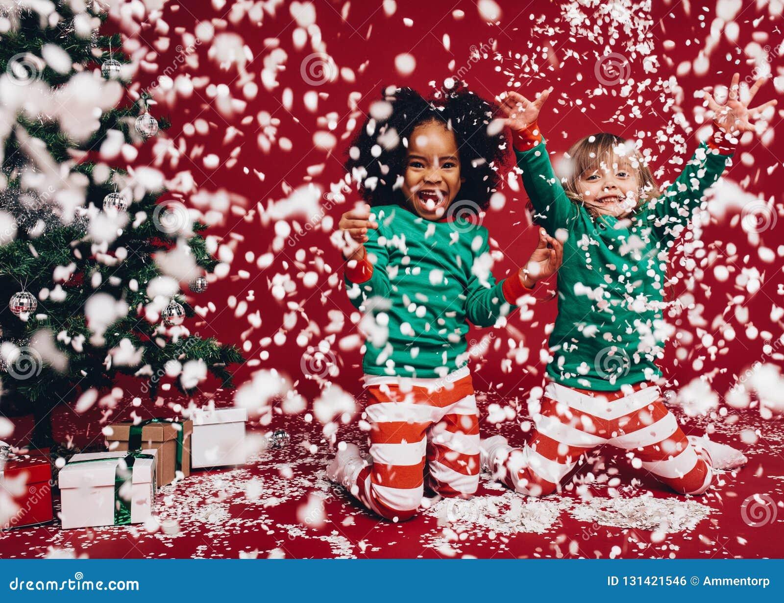 2 маленькой девочки в костюмах рождества играя с искусственными хлопьями снега Дети имеющ наслаждаться потехи искусственные снежн