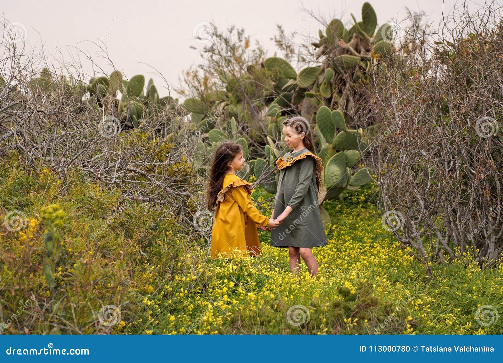 2 маленькой девочки в ретро винтажных платьях держа руки стоят в кактусах и overgrown ветвях