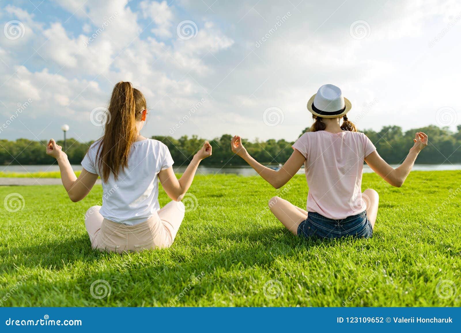 2 маленькой девочки делая йогу представляют внешнее, йога на заходе солнца в парке, заднем взгляде
