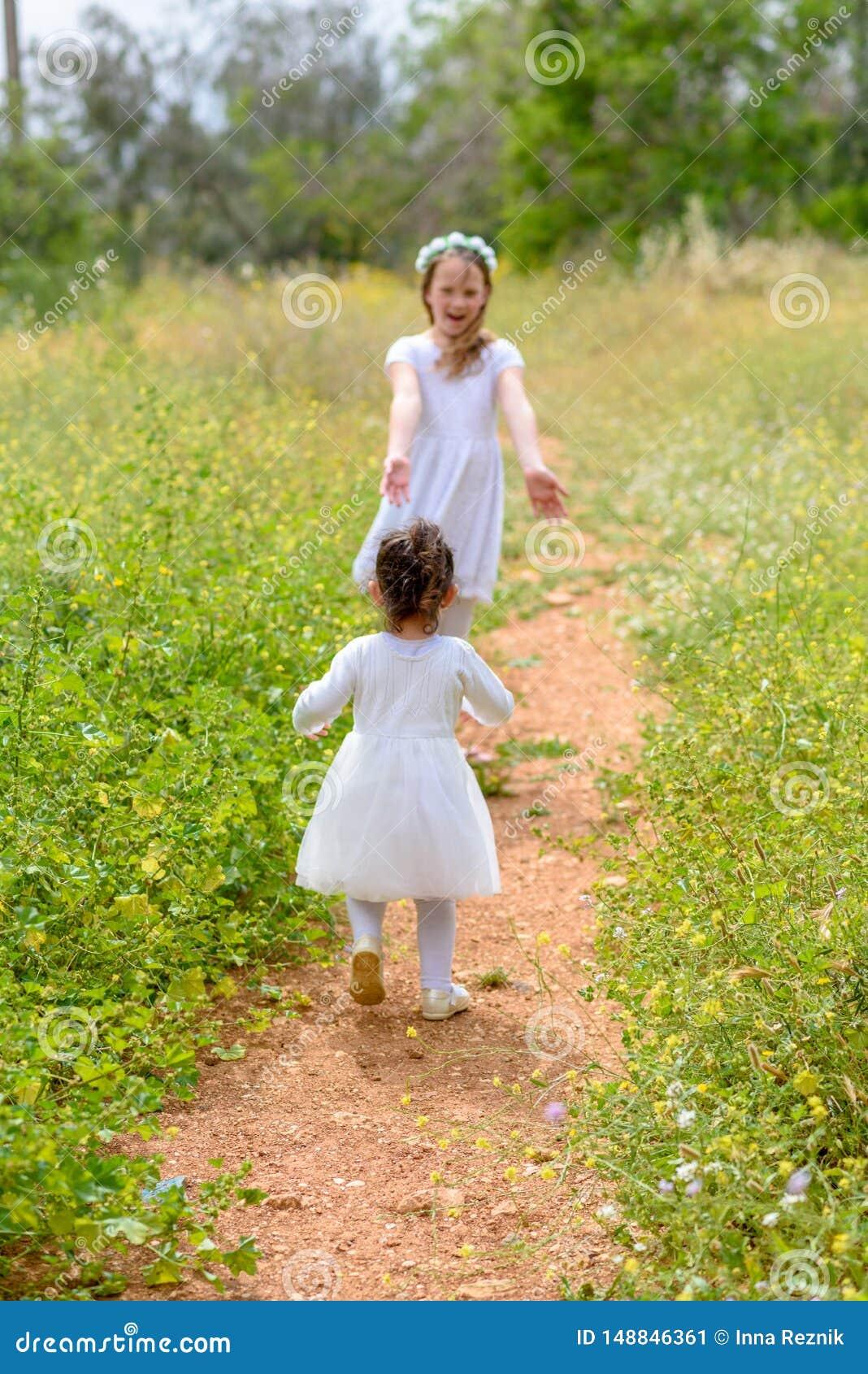 2 маленькой девочки играя ход на зеленом лесе на открытом воздухе