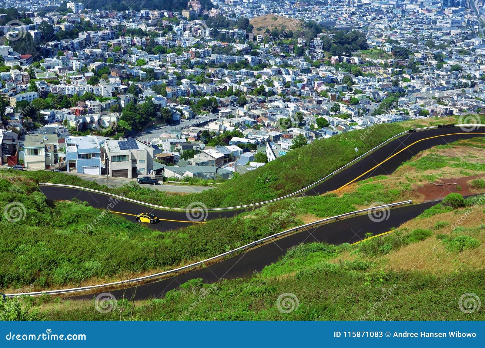 Малый желтый автомобиль сигналя вдоль гористой дороги