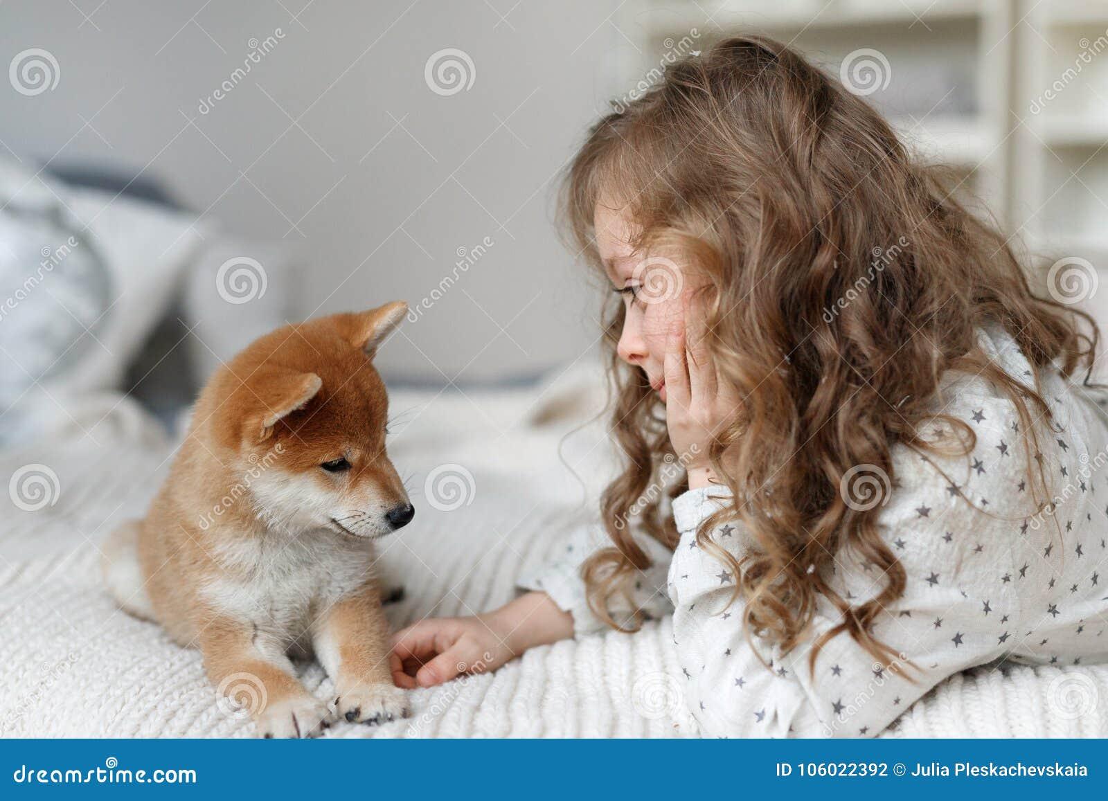 Малый женский ребенк имеет длинные игры вьющиеся волосы с ее любимой собакой на кровати, был радостен потратить время с любимчико