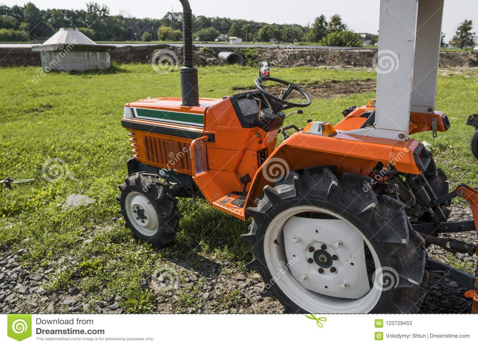Малый мини оранжевый трактор стоит на дворе фермы на зеленой траве и ждет работу для того чтобы начать