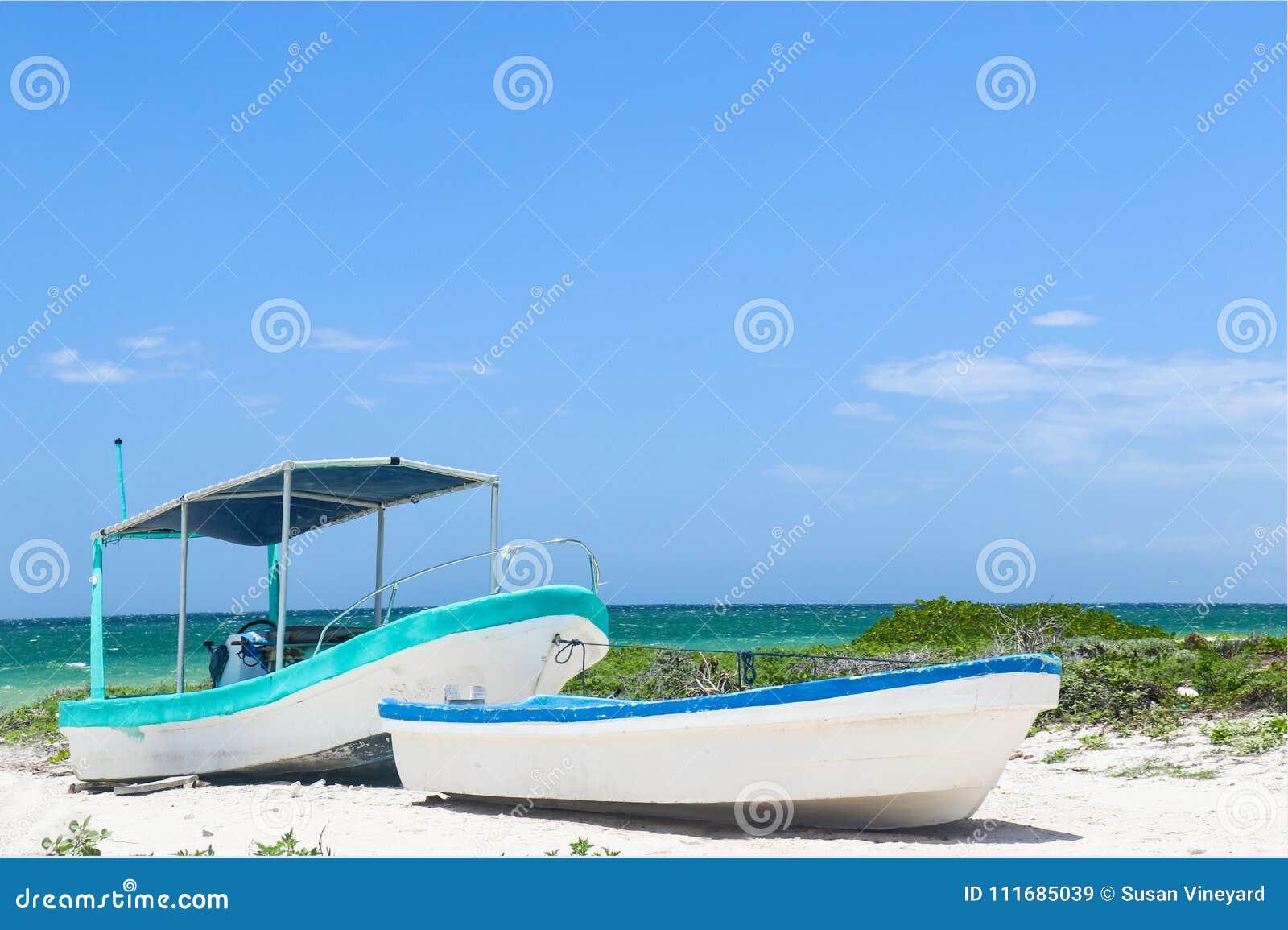 2 малых рыбацкой лодки связанной совместно на тропическом пляже