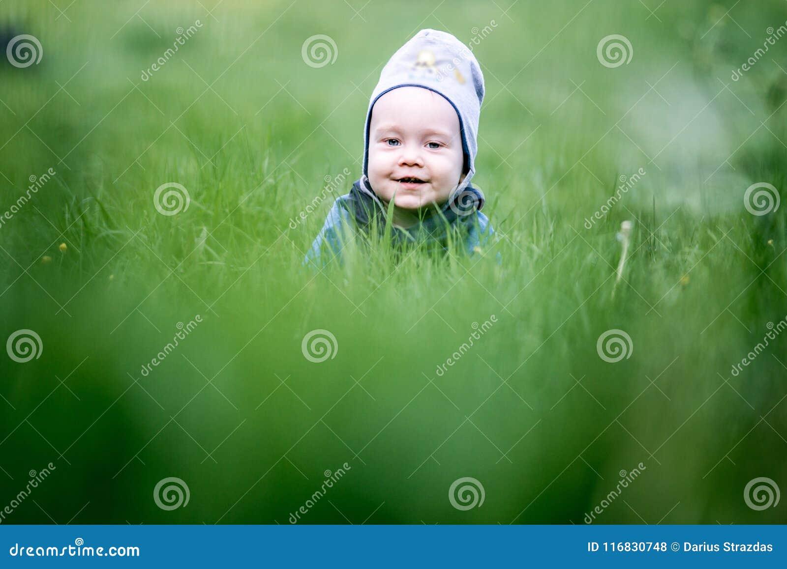 Малыш ребенк в играть травы пряча