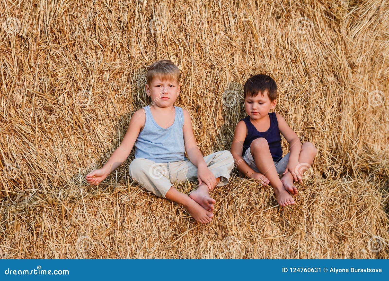 2 мальчика сидят на большом амбаре