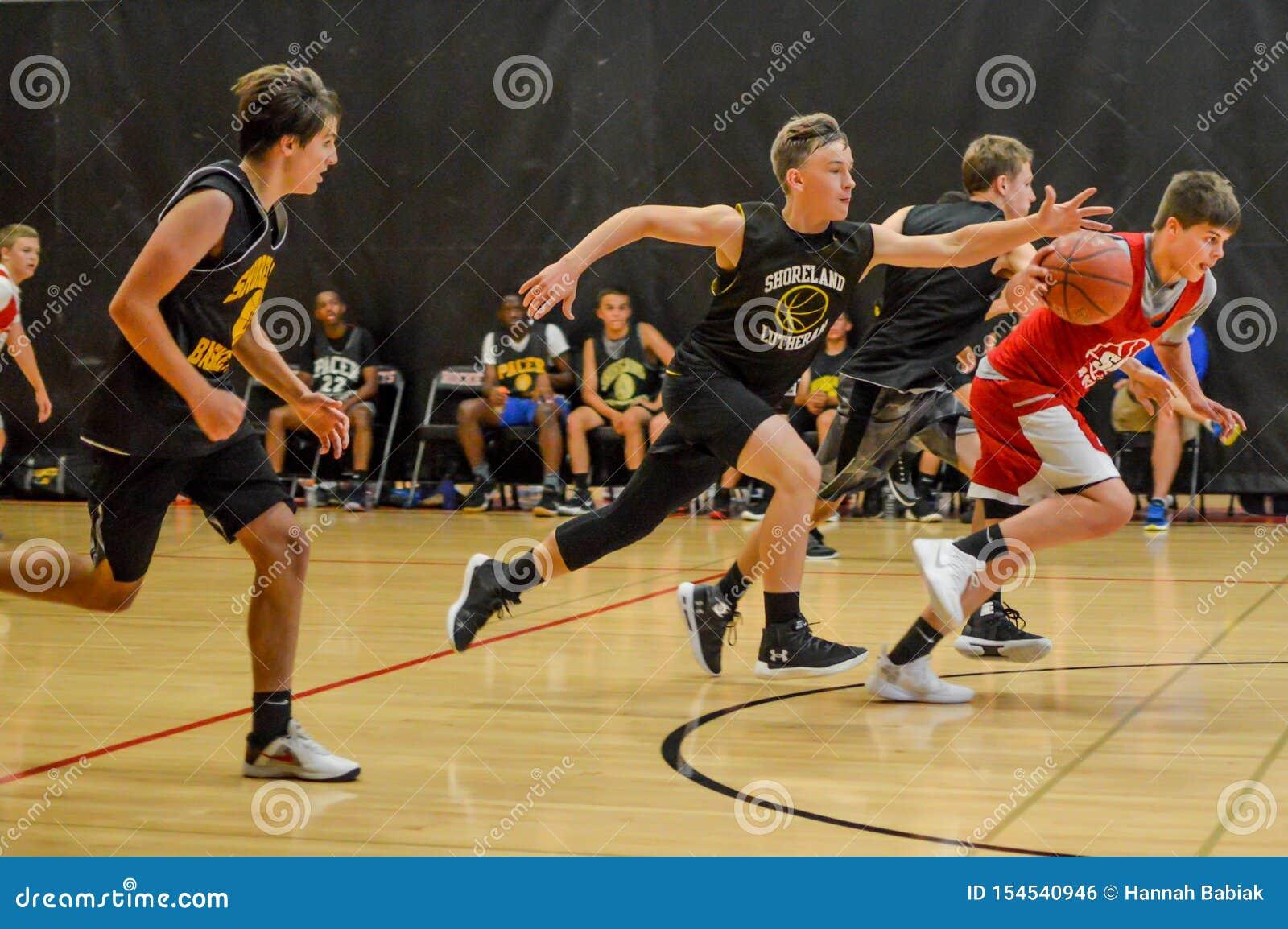 Мальчики средней школы играя баскетбол