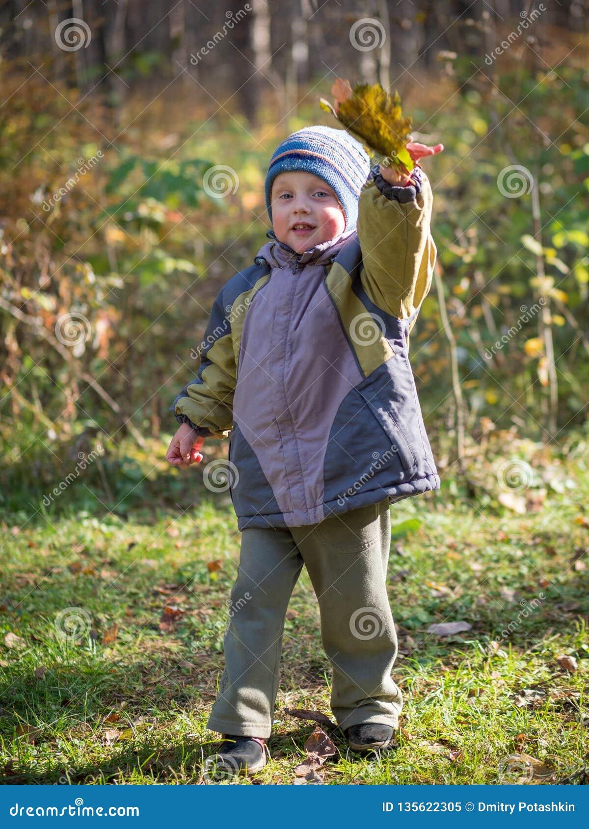 Мальчик бросает листья в парке осени