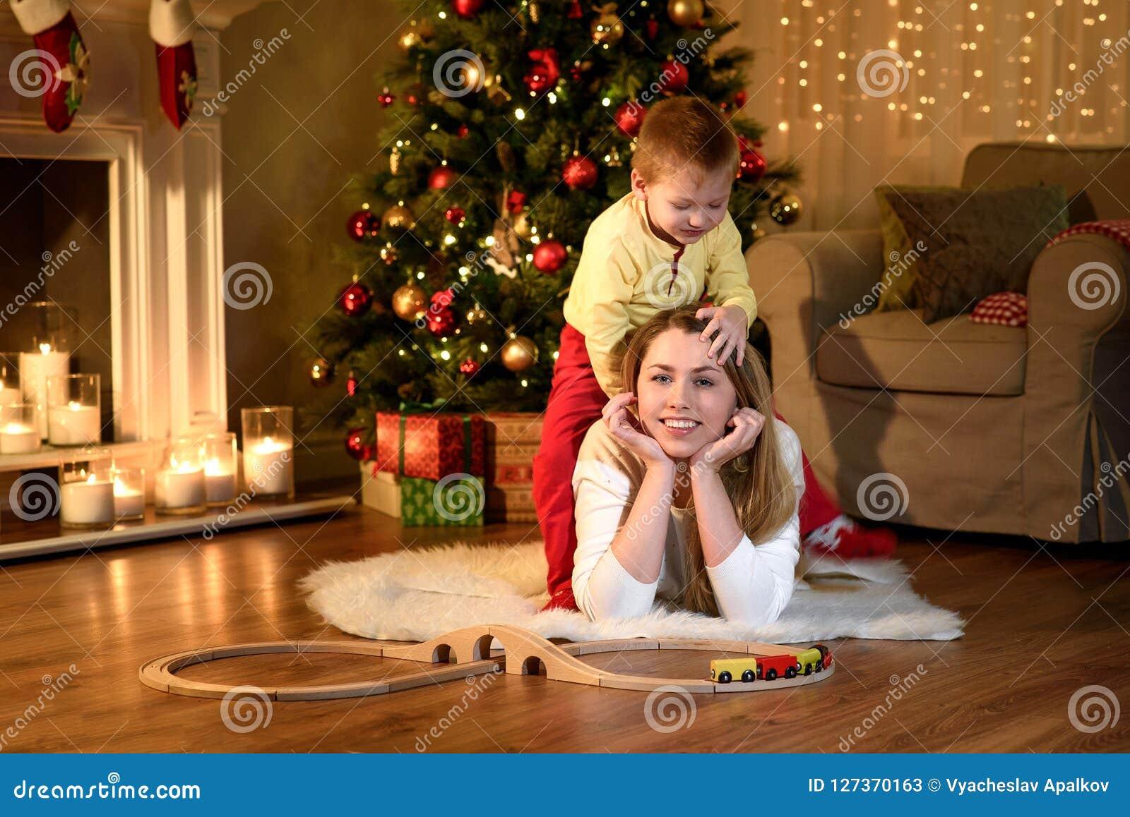 Мальчик взбирается его лежа задняя часть ` s мамы