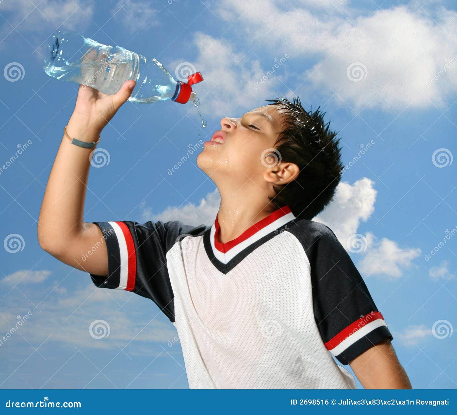 мальчик выпивая вне испытывающий жажду воду