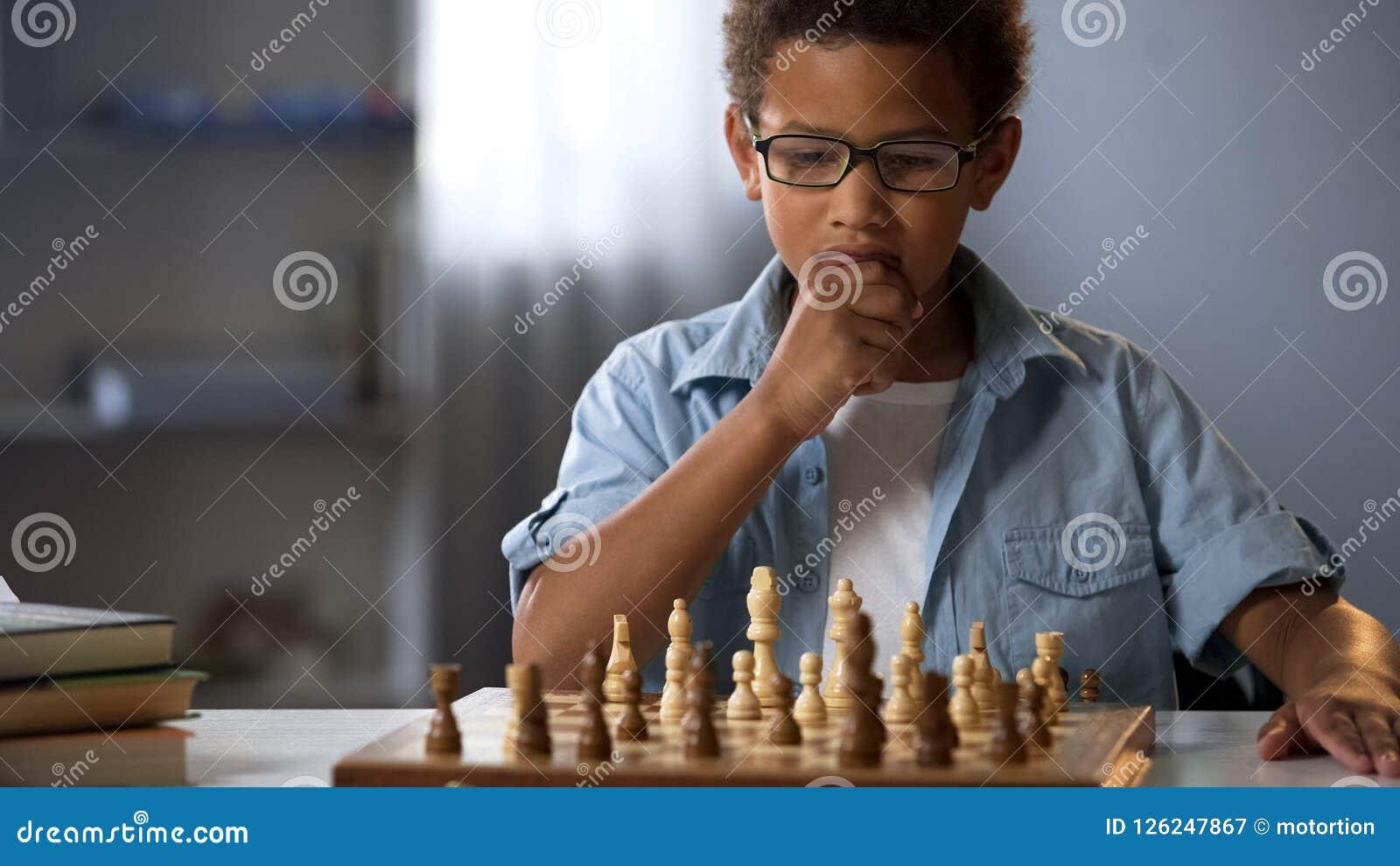 Мальчик думая на движении шахмат, умном хобби, развитии логики, отдыхе