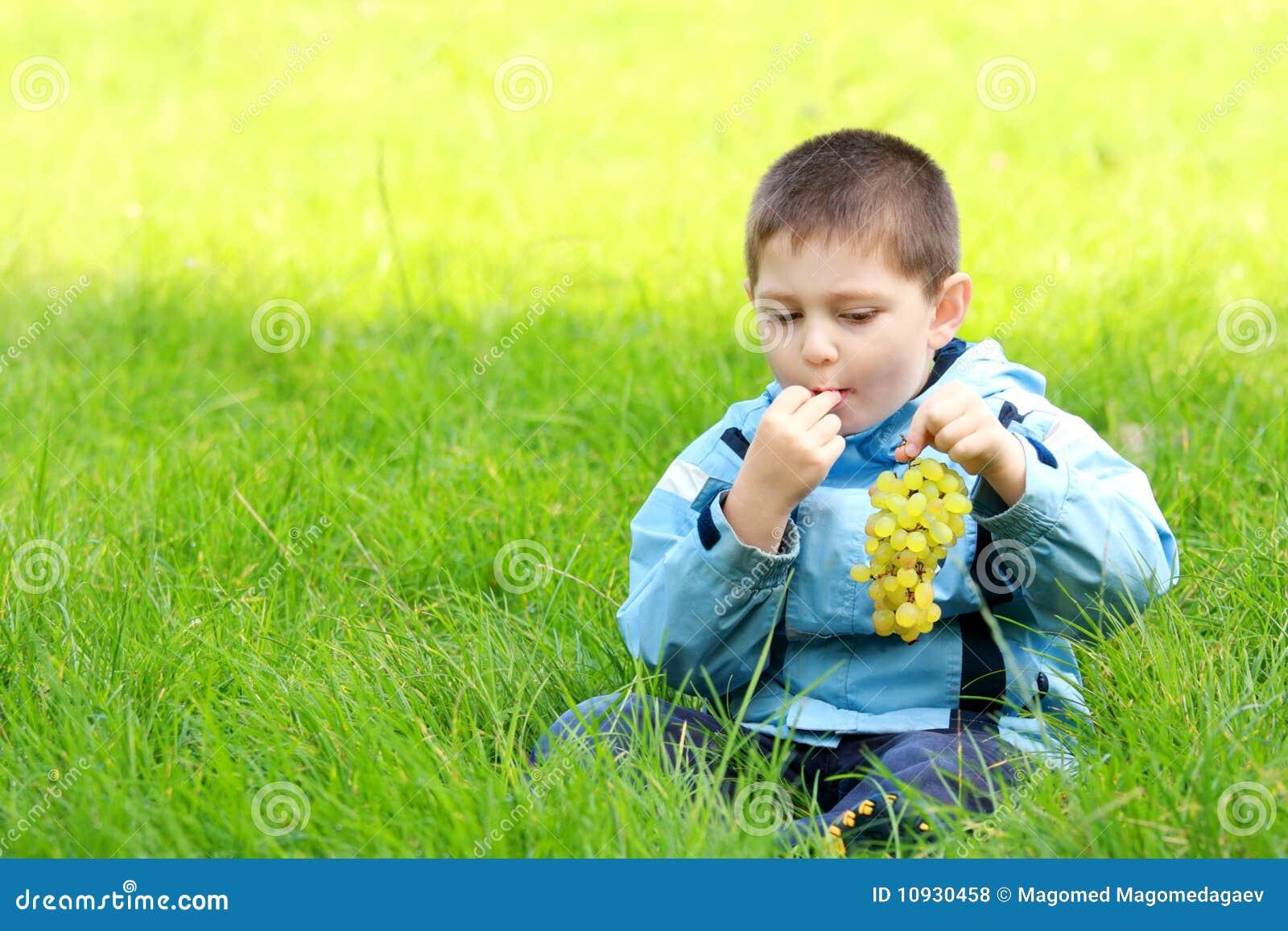 мальчик ест лужок виноградин