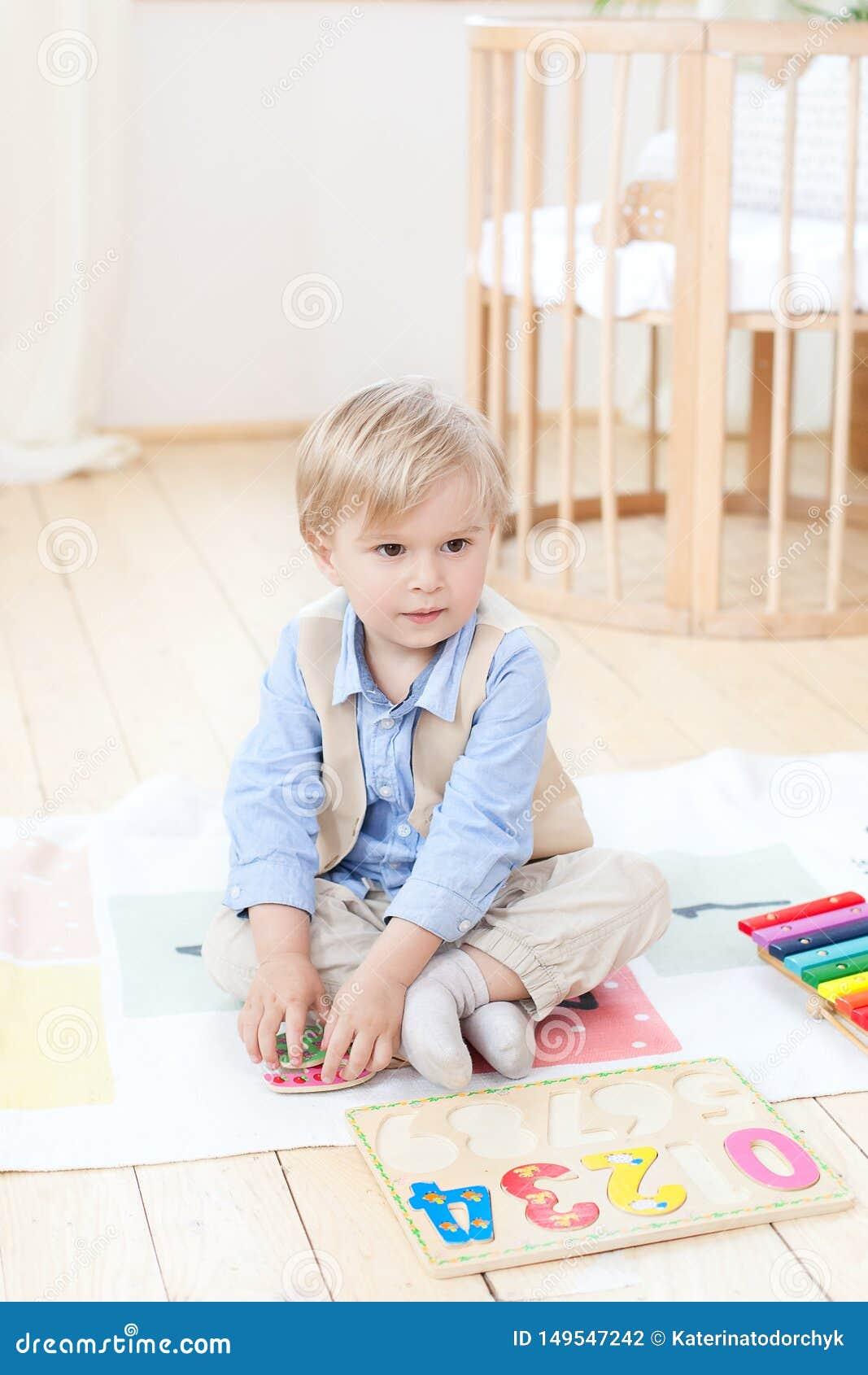 Мальчик играет с деревянными игрушками дома Воспитательные деревянные игрушки для ребенка Портрет мальчика сидя на поле в ребенке