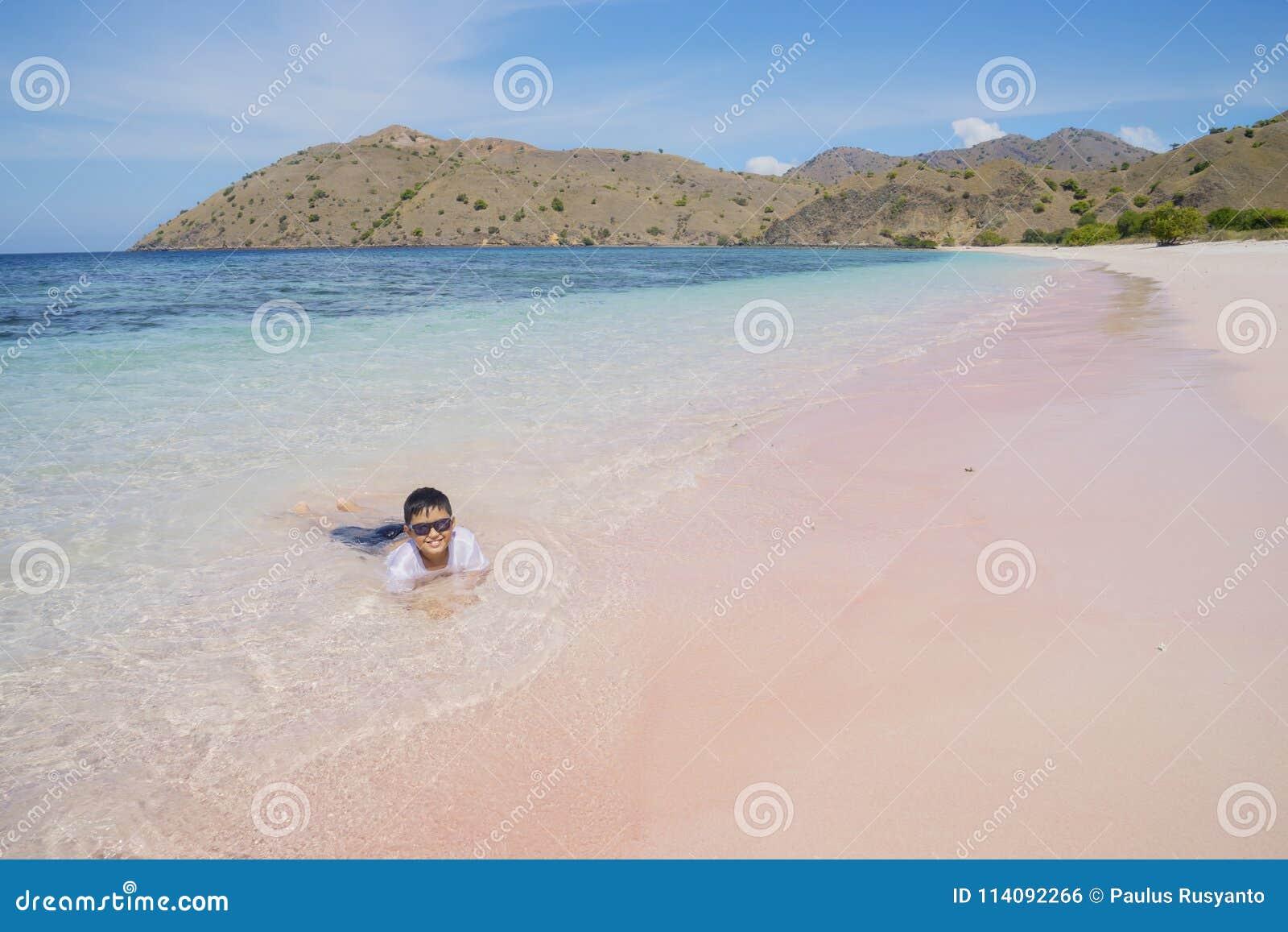 Мальчик играя волну на розовом пляже