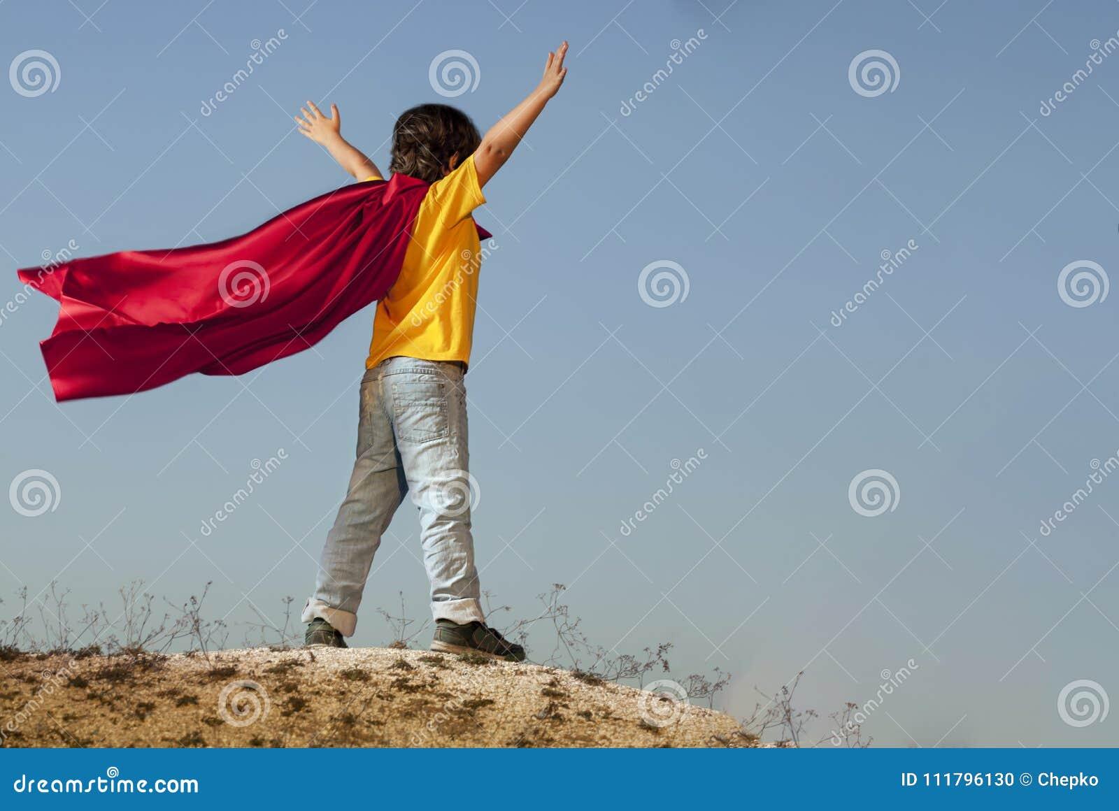 Мальчик играя супергероев на предпосылке неба, подростковый супергероя