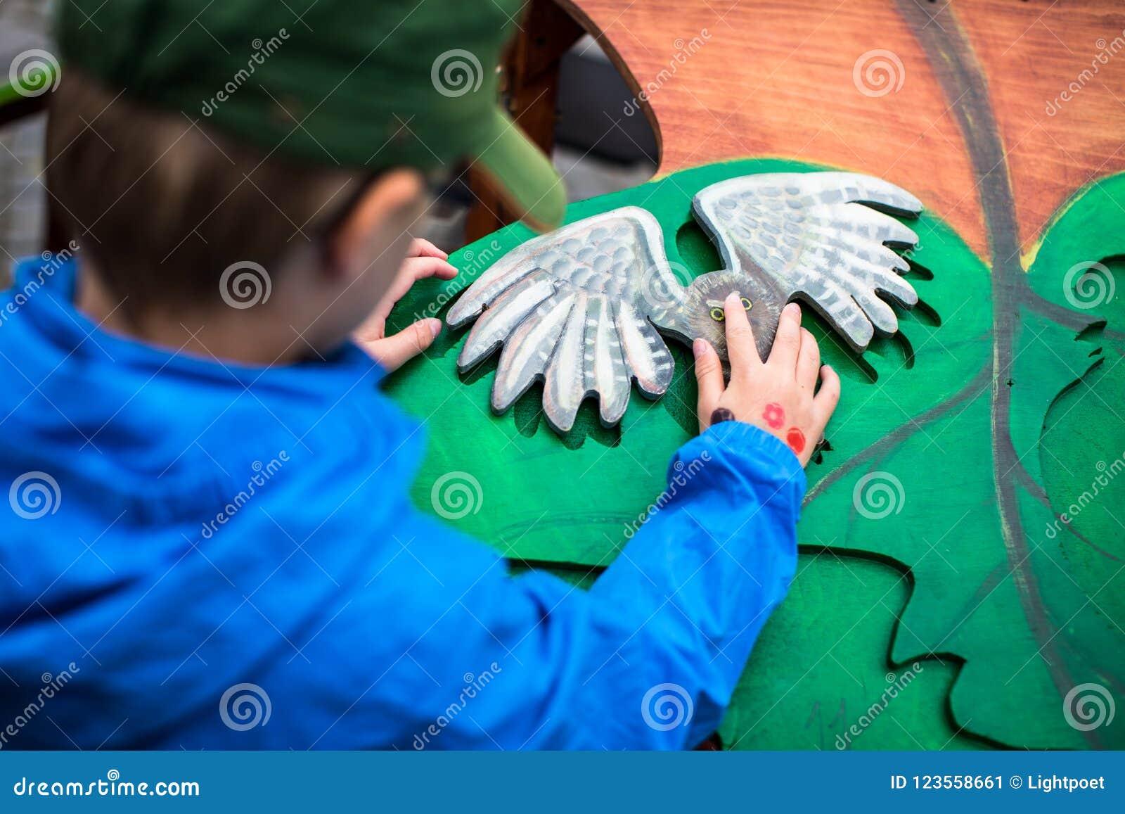 Мальчик играя с деревянными игрушками