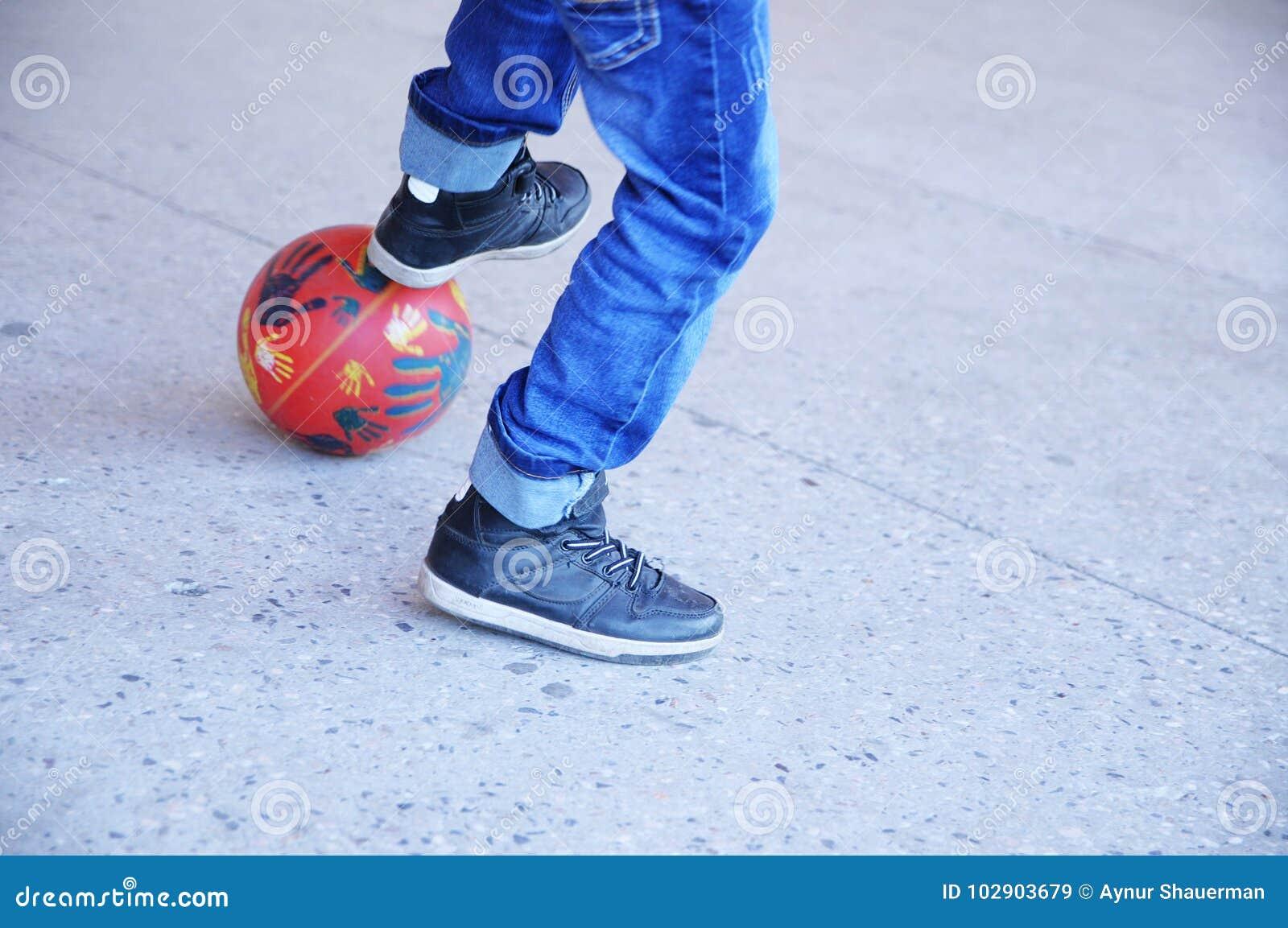 Мальчик играя футбол, ноги ` s подростка с шариком на асфальте, игроке футбольной команды, тренируя внешний, активный образ жизни