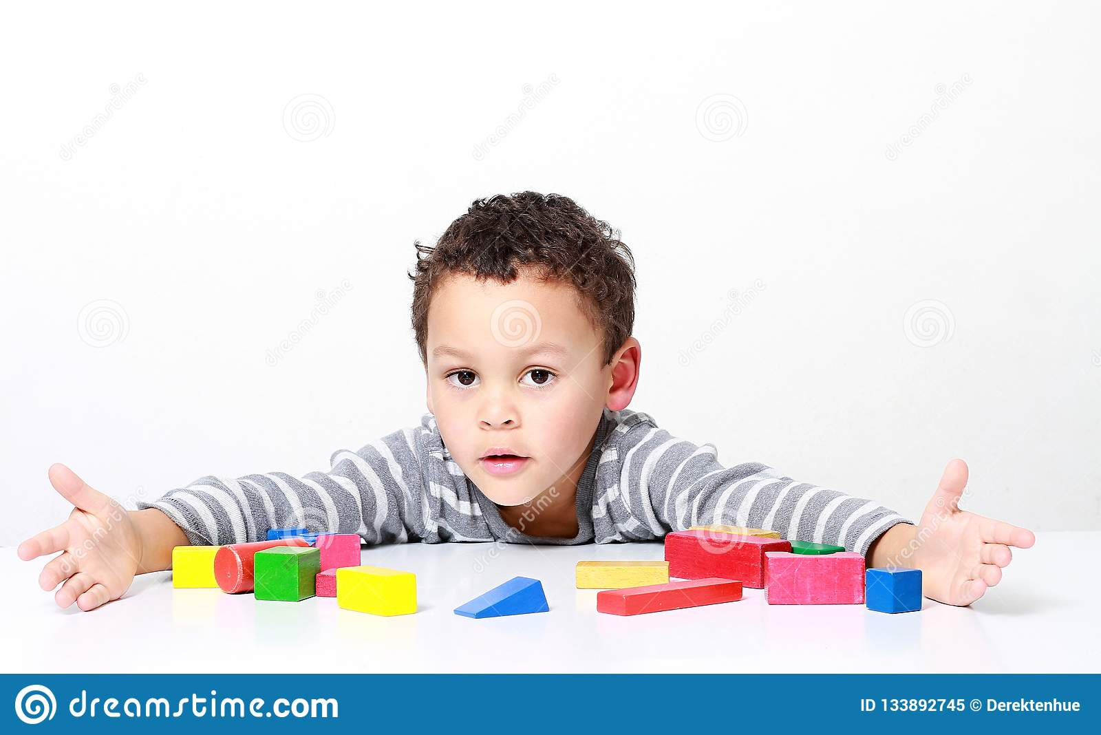 Мальчик испытывая его творческие способности путем построение башен со строительными блоками игрушки