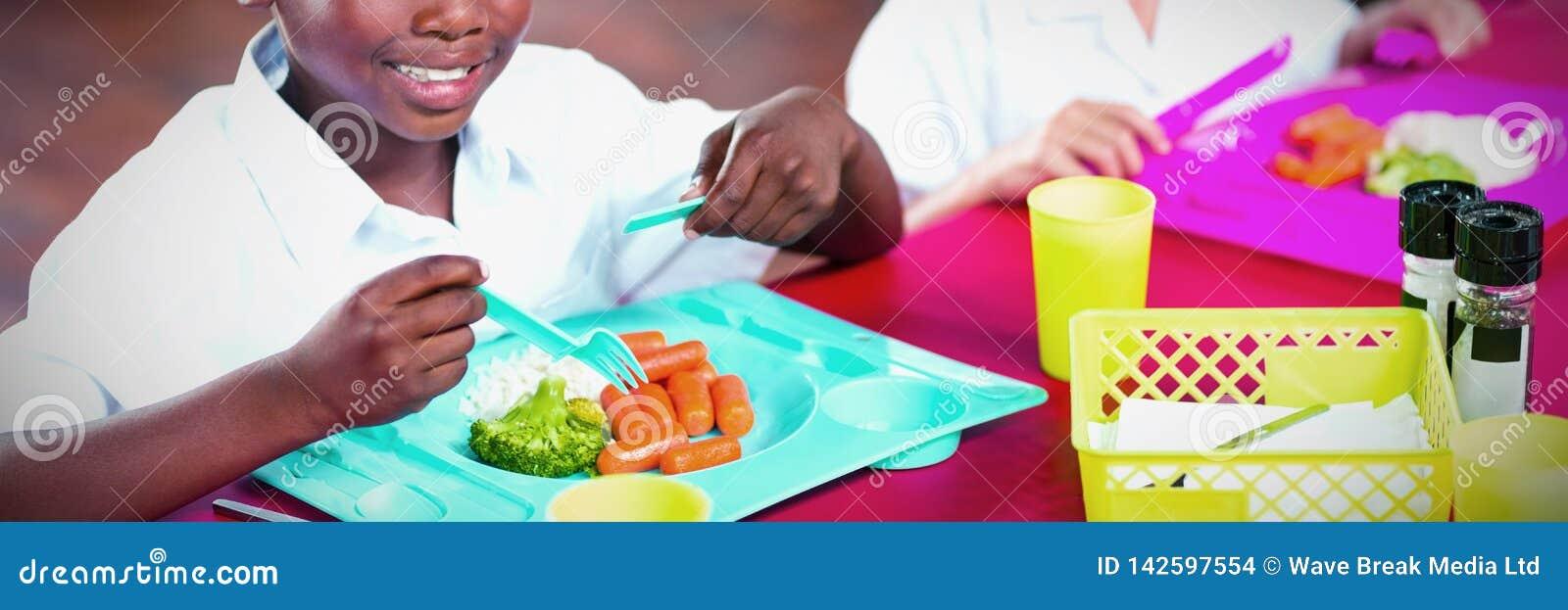 Мальчик и девушка в школьных формах имея обед в школьном кафетерии