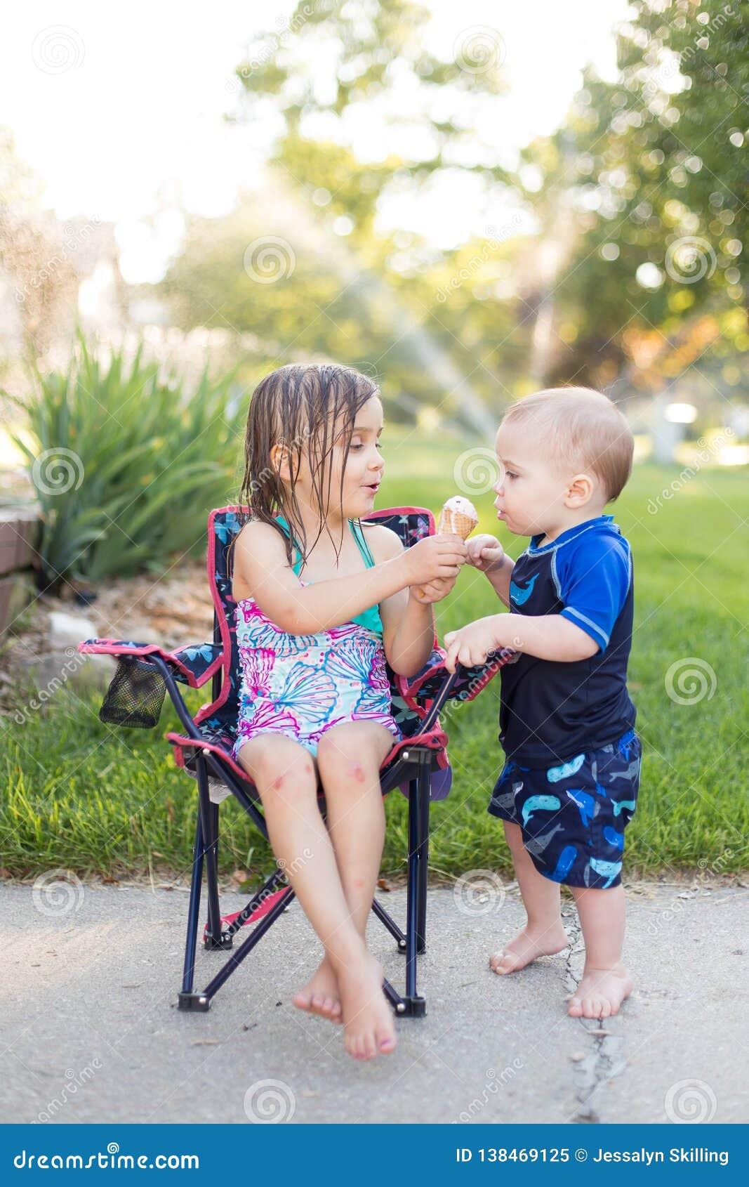 Мальчик и девушка есть мороженое