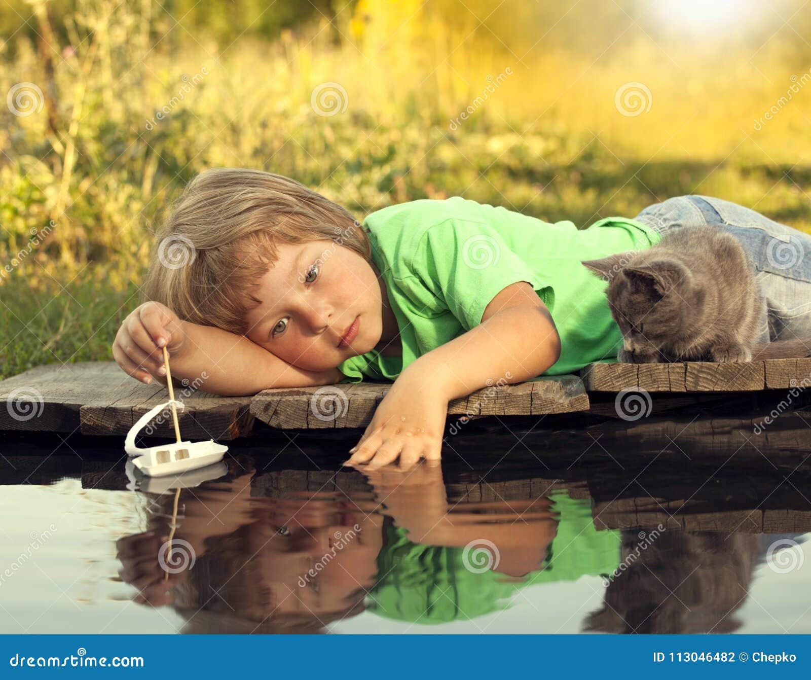 Мальчик и его любимый котенок играя с шлюпкой от пристани в пруде