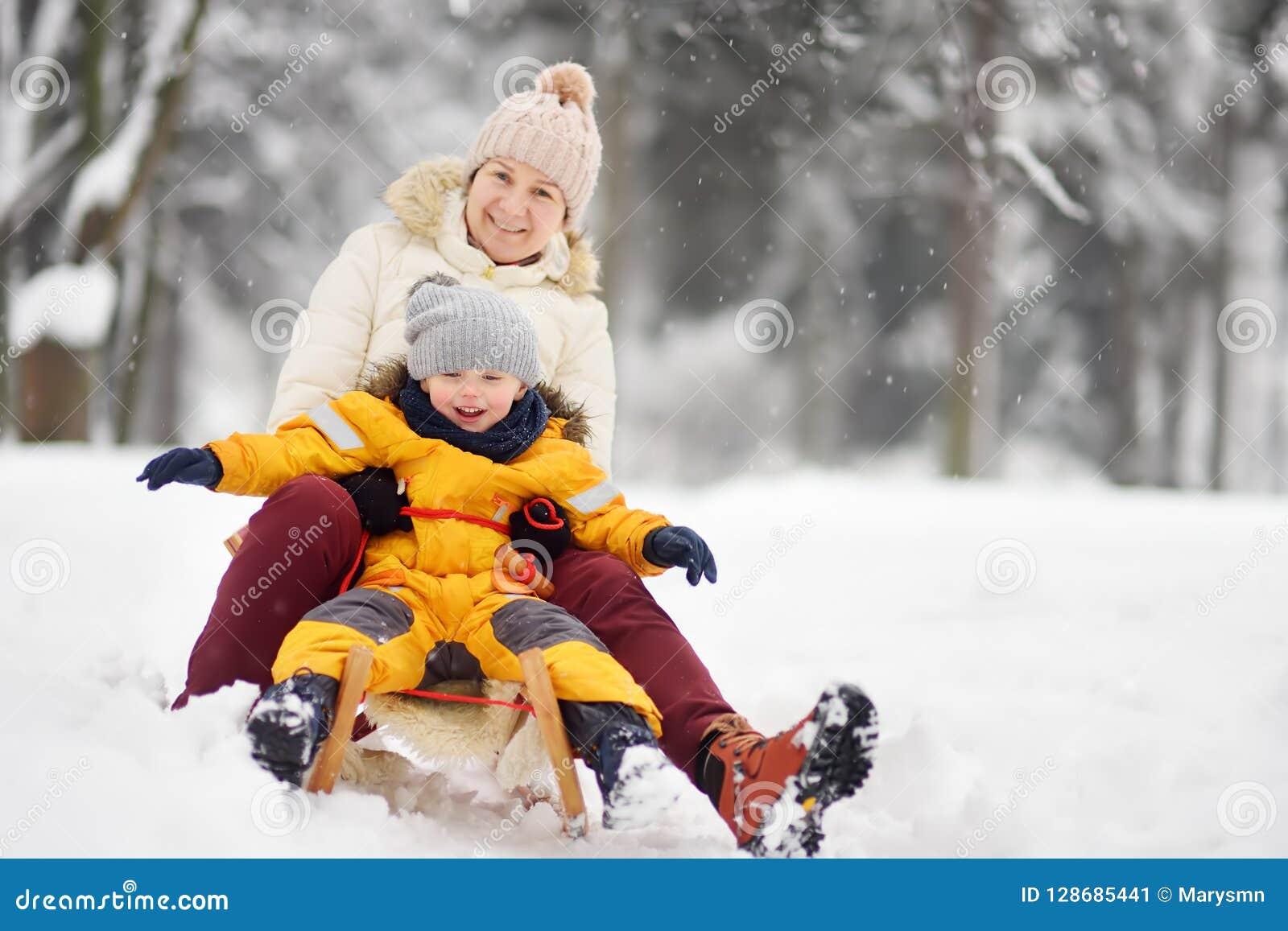 Мальчик и мать/бабушка/няня сползая в парк во время снежности