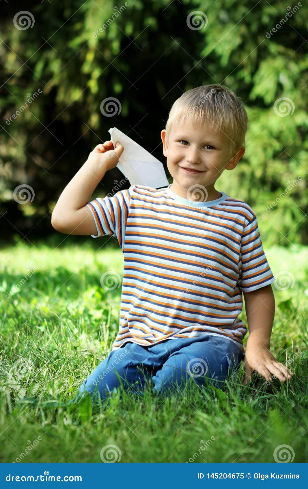 Мальчик 7 лет сидит на траве с бумажным самолетом в его руке o Bokeh