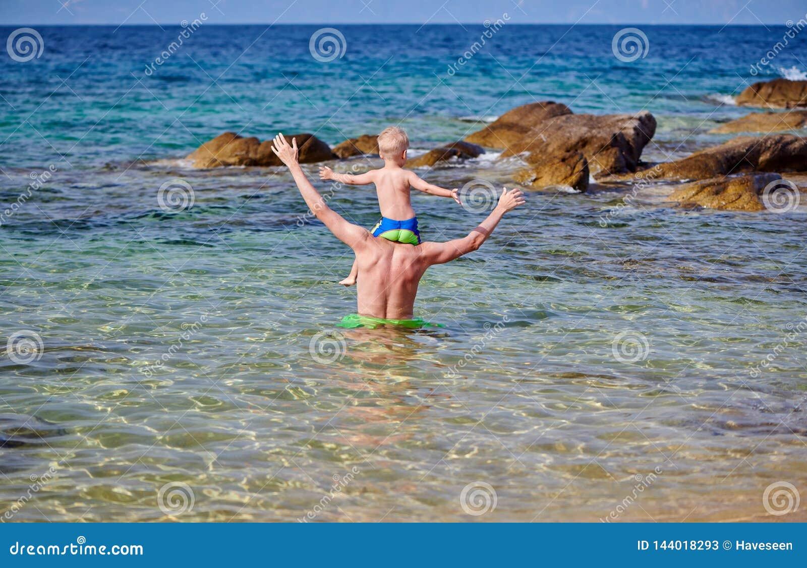 Мальчик малыша на плечах отца на пляже