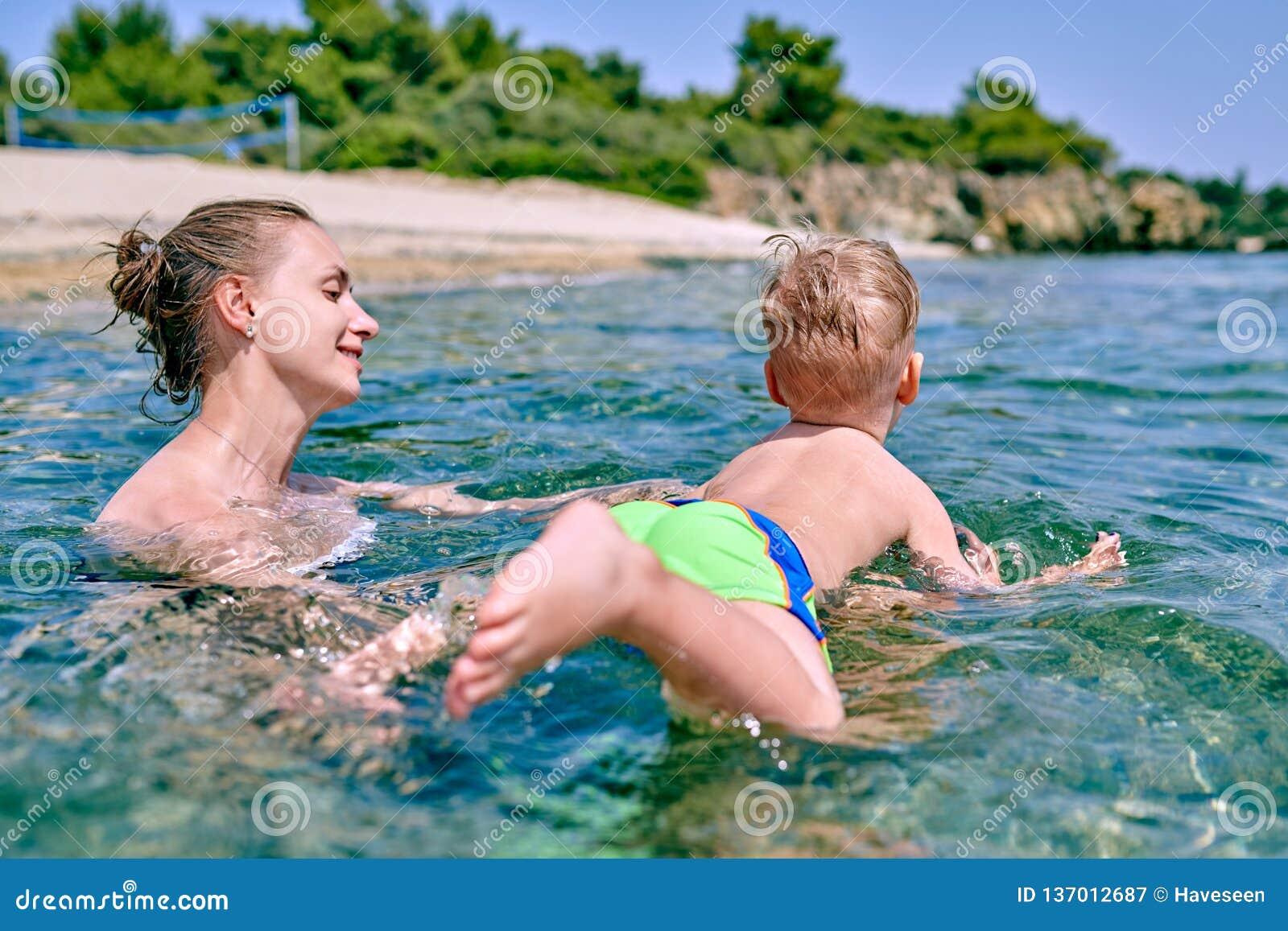 Мальчик малыша учит поплавать с матерью