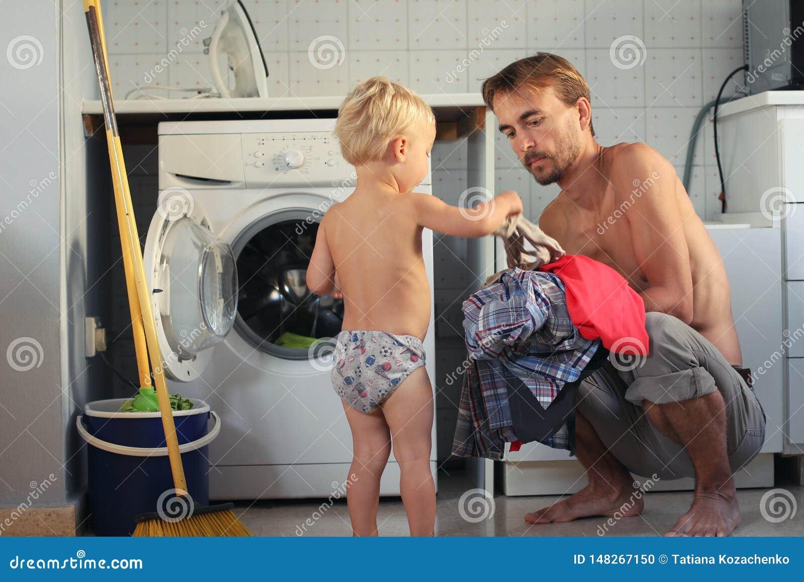 Мальчик милого малыша белокурый помогает его отцу положить прачечную в стиральную машину Домашнее хозяйство семьи, мужская концеп