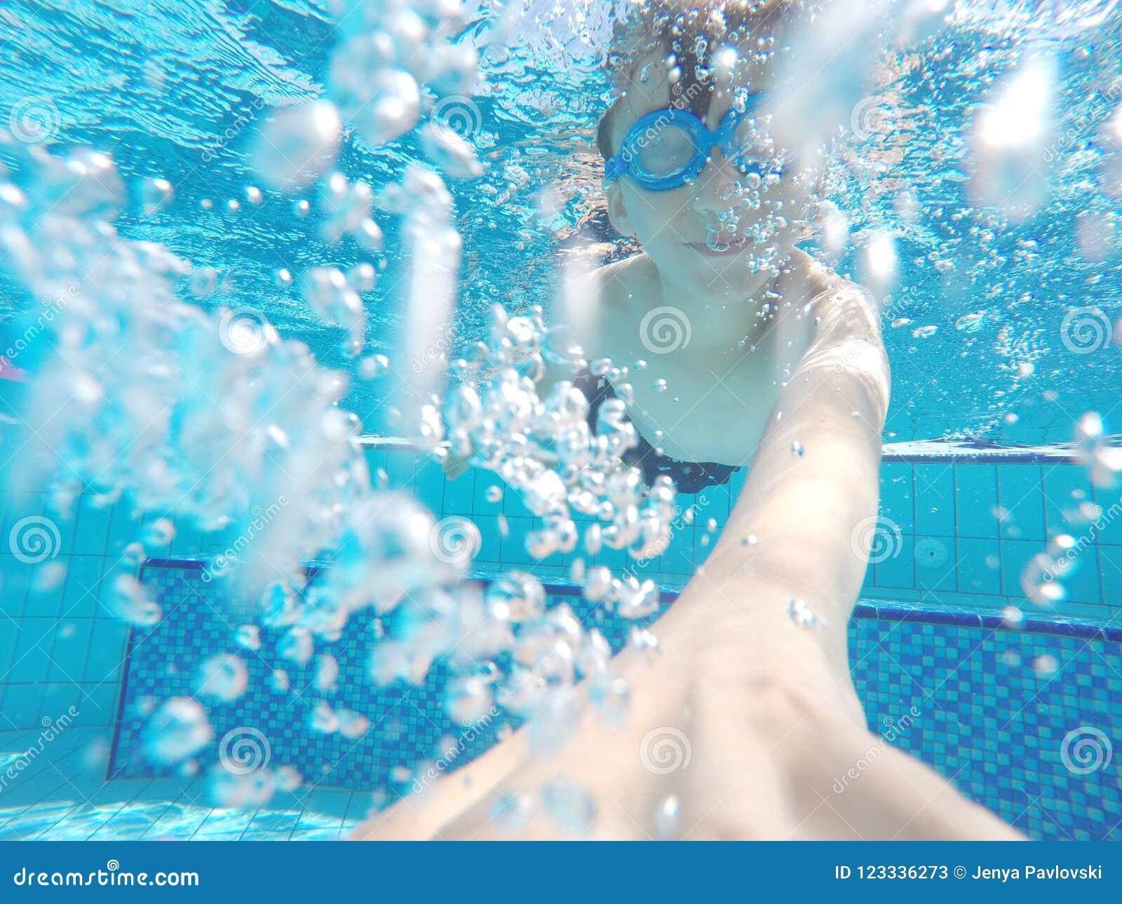 Мальчик плавает под водой в бассейне