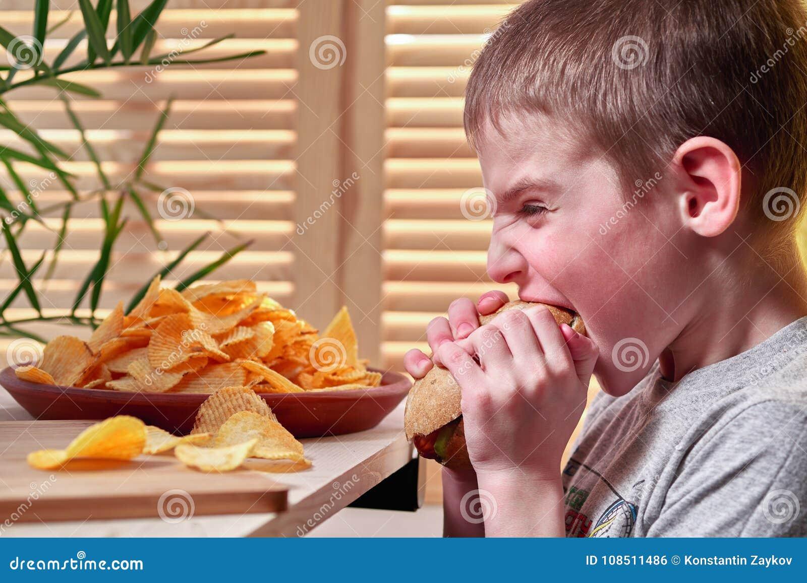 Мальчик полно страстного желания сдерживает очень вкусный большой хот-дога Ребенок ест в фаст-фуде