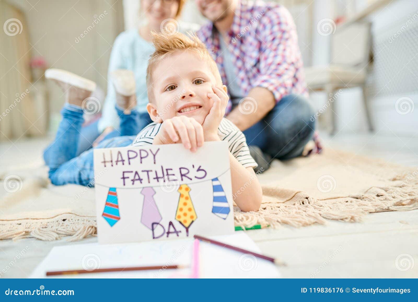 Мальчик представляя с Handmade поздравительной открыткой