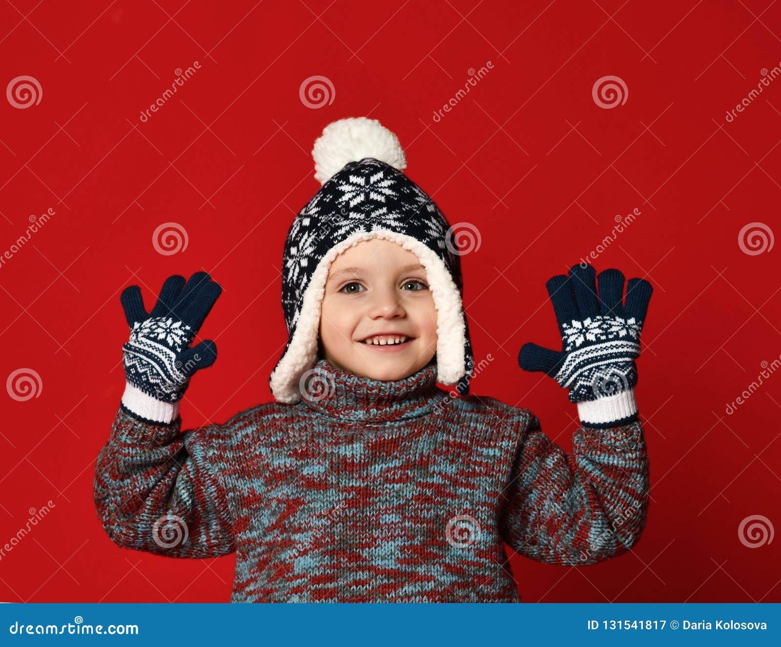 Мальчик ребенка в связанной шляпе и свитере и mittens имея потеху над красочной красной предпосылкой