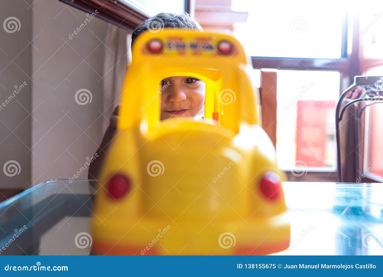Мальчик ребенка играя с игрушкой школьного автобуса внутри помещения