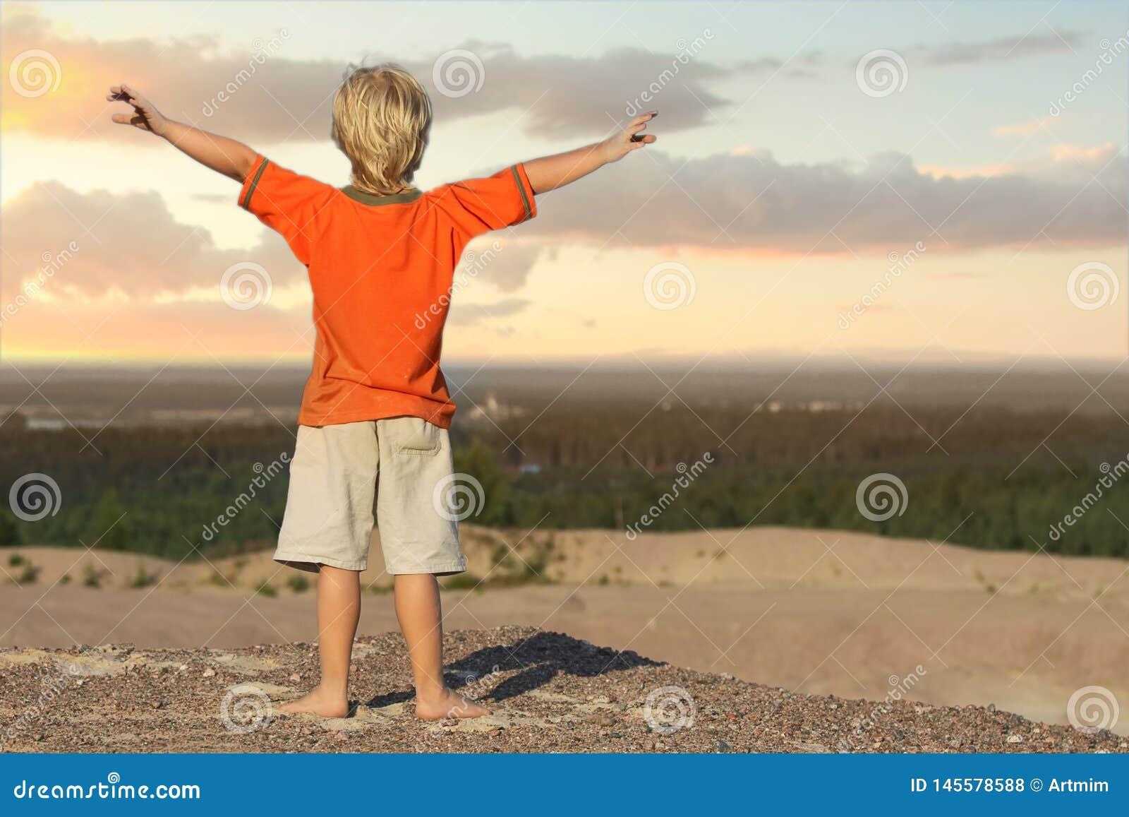Мальчик ребенк смотря восход солнца на горе песка