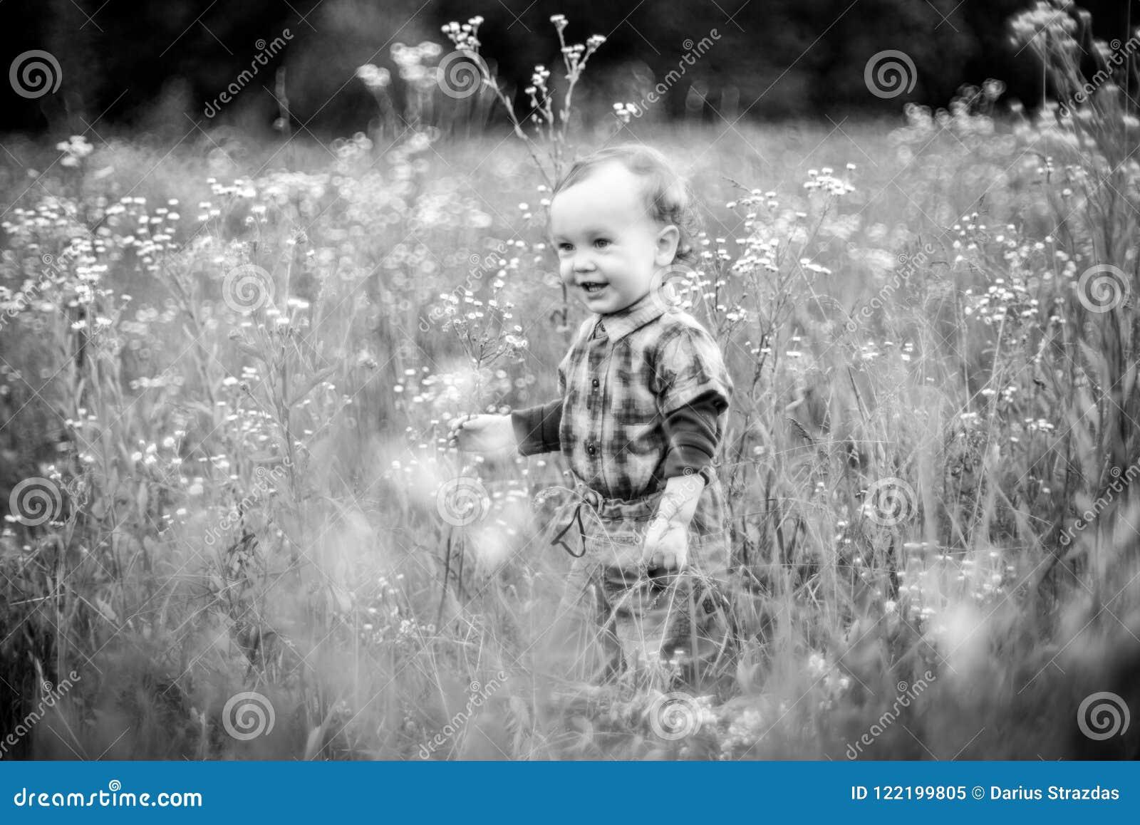 Мальчик самостоятельно в высокорослом поле травы