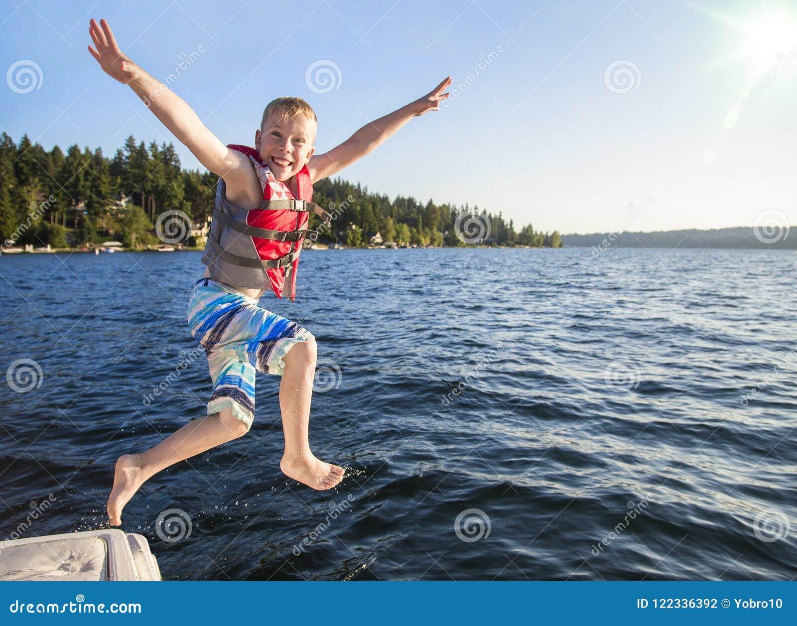 Мальчик скача в красивое озеро горы Иметь потеху на летних каникулах