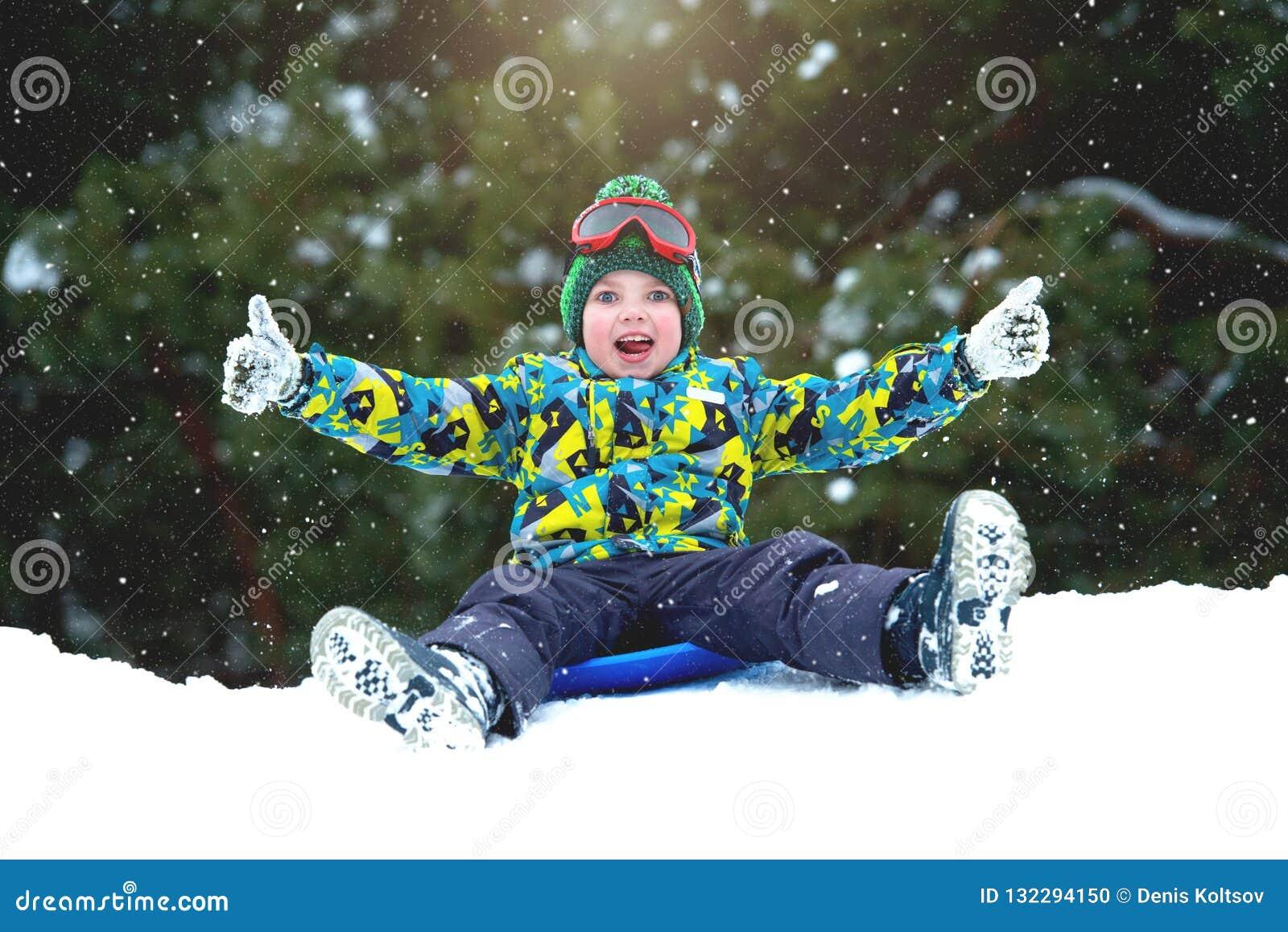 Мальчик sledding в потехе зимы снежного леса на открытом воздухе на каникулы рождества