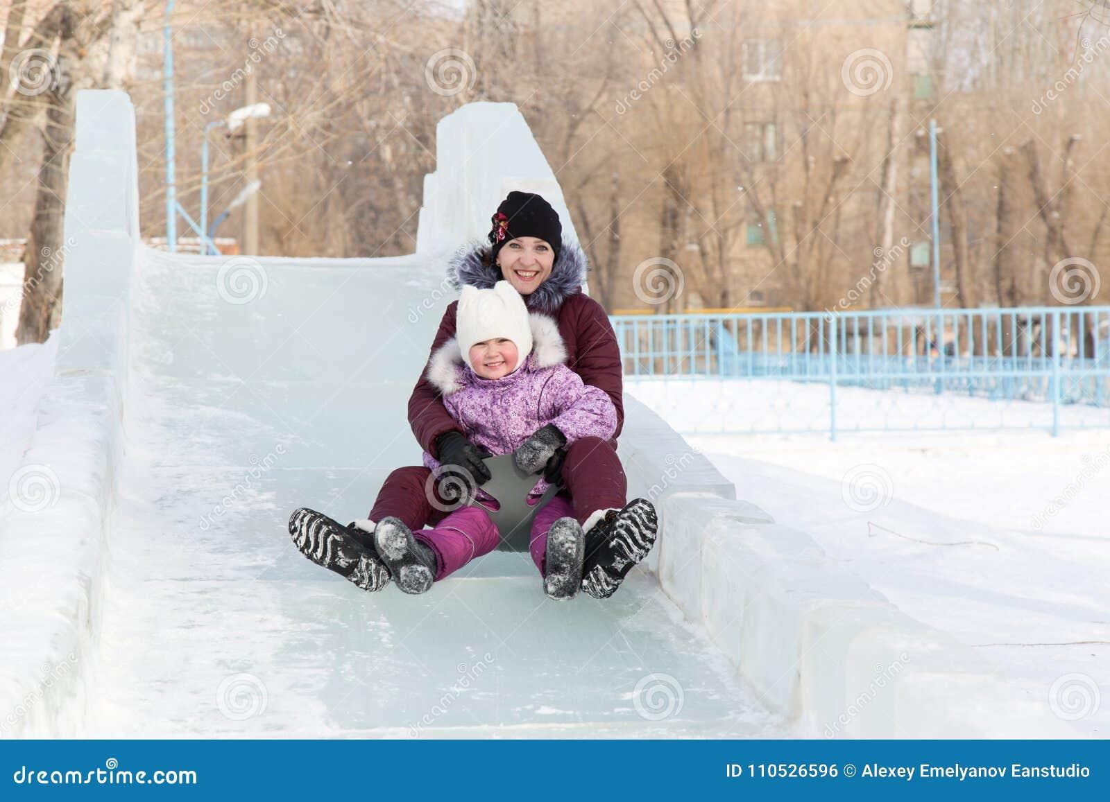 Мама и дочь едут от снежной горы
